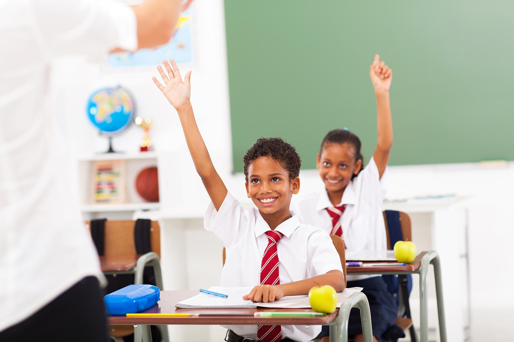 Children in uniform raising their hands for the teacher