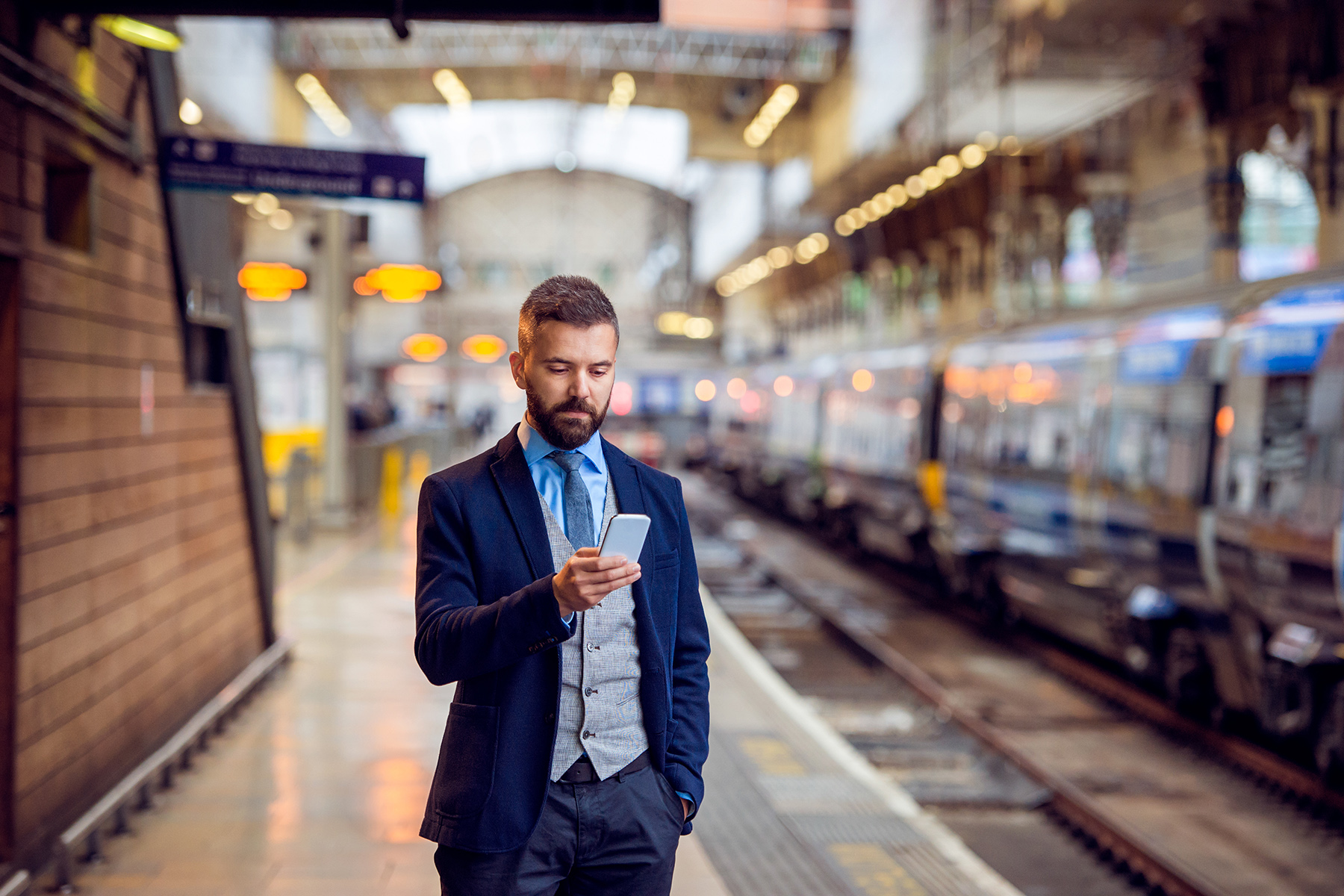 Businessman using his phone in a metro station