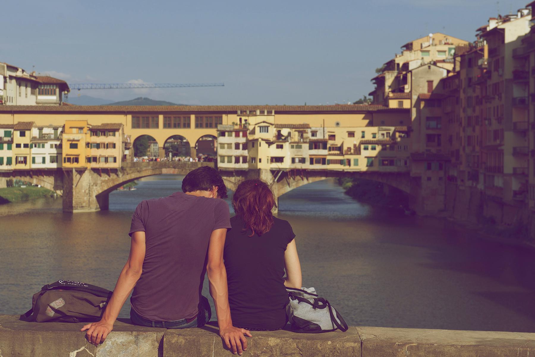 A couple sitting on a bridge in Firenze