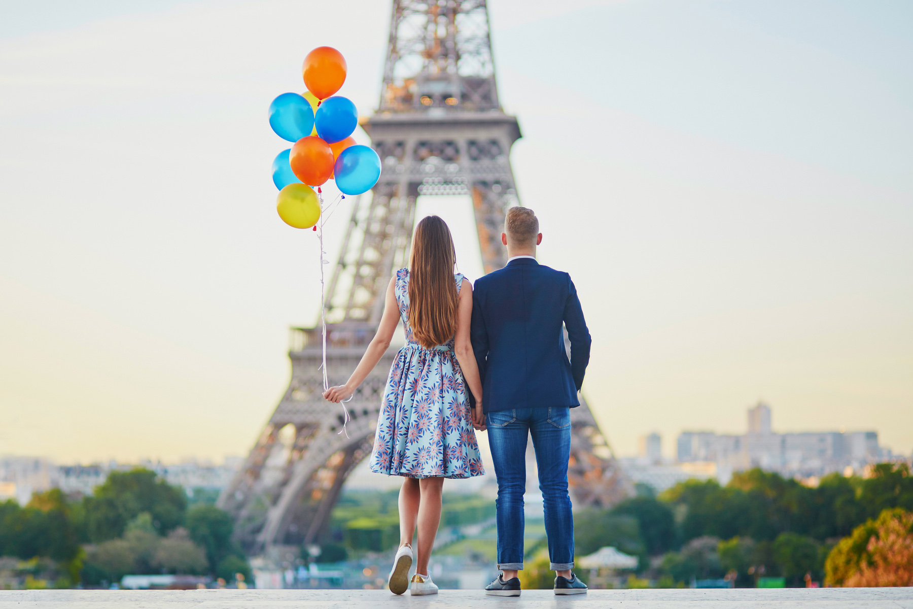 A couple holding hands in front of the Eiffel Tower
