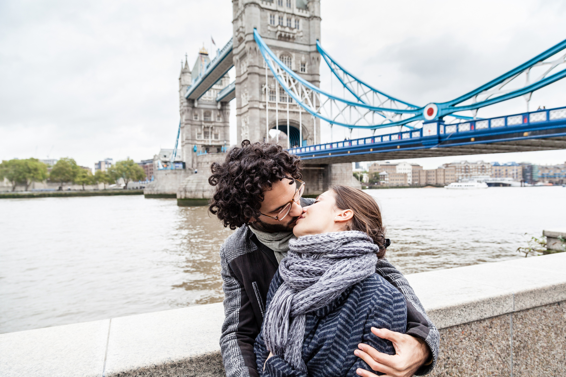 A couple kissing in front of the Tower Bridge