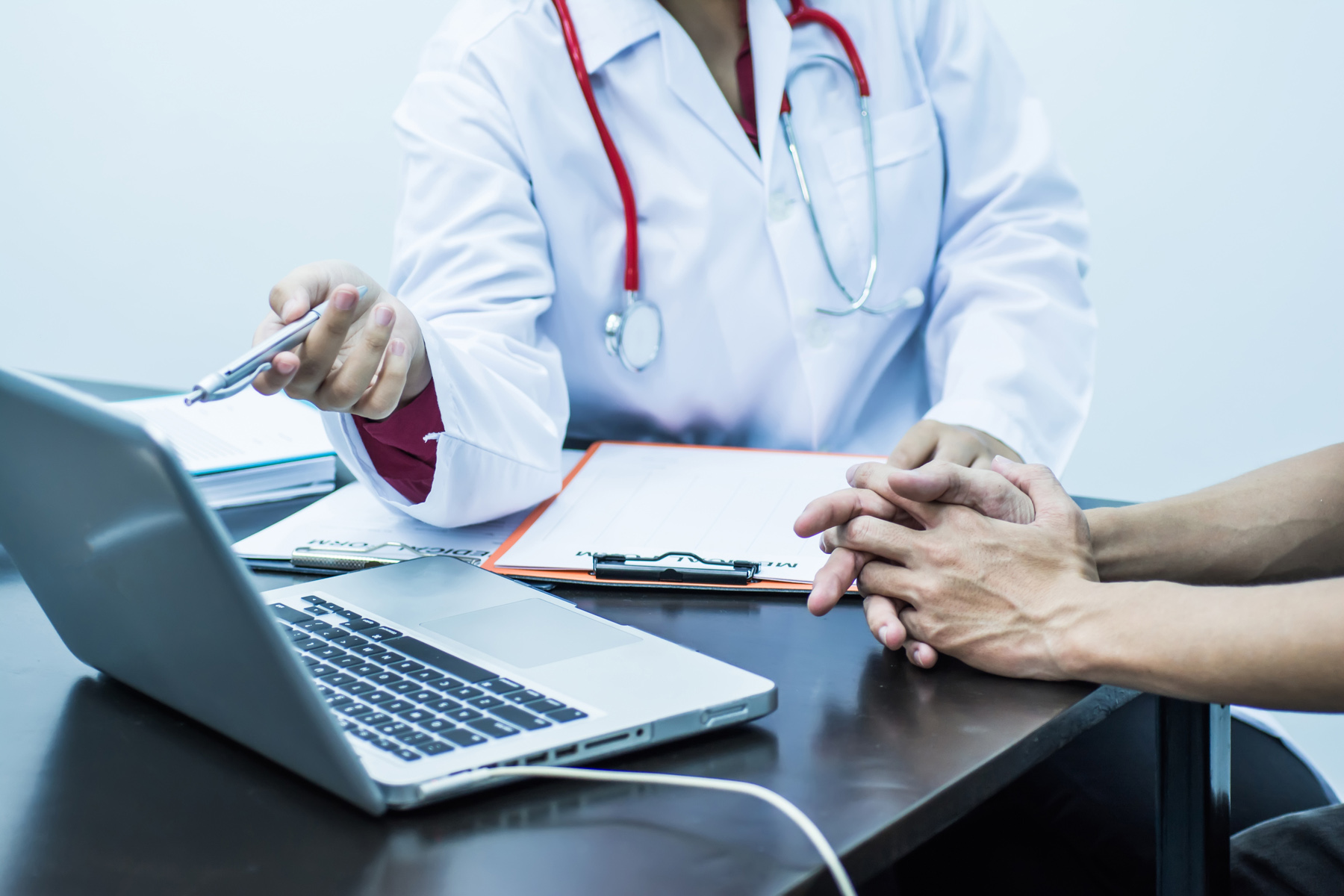 A doctor and a patient looking at a laptop