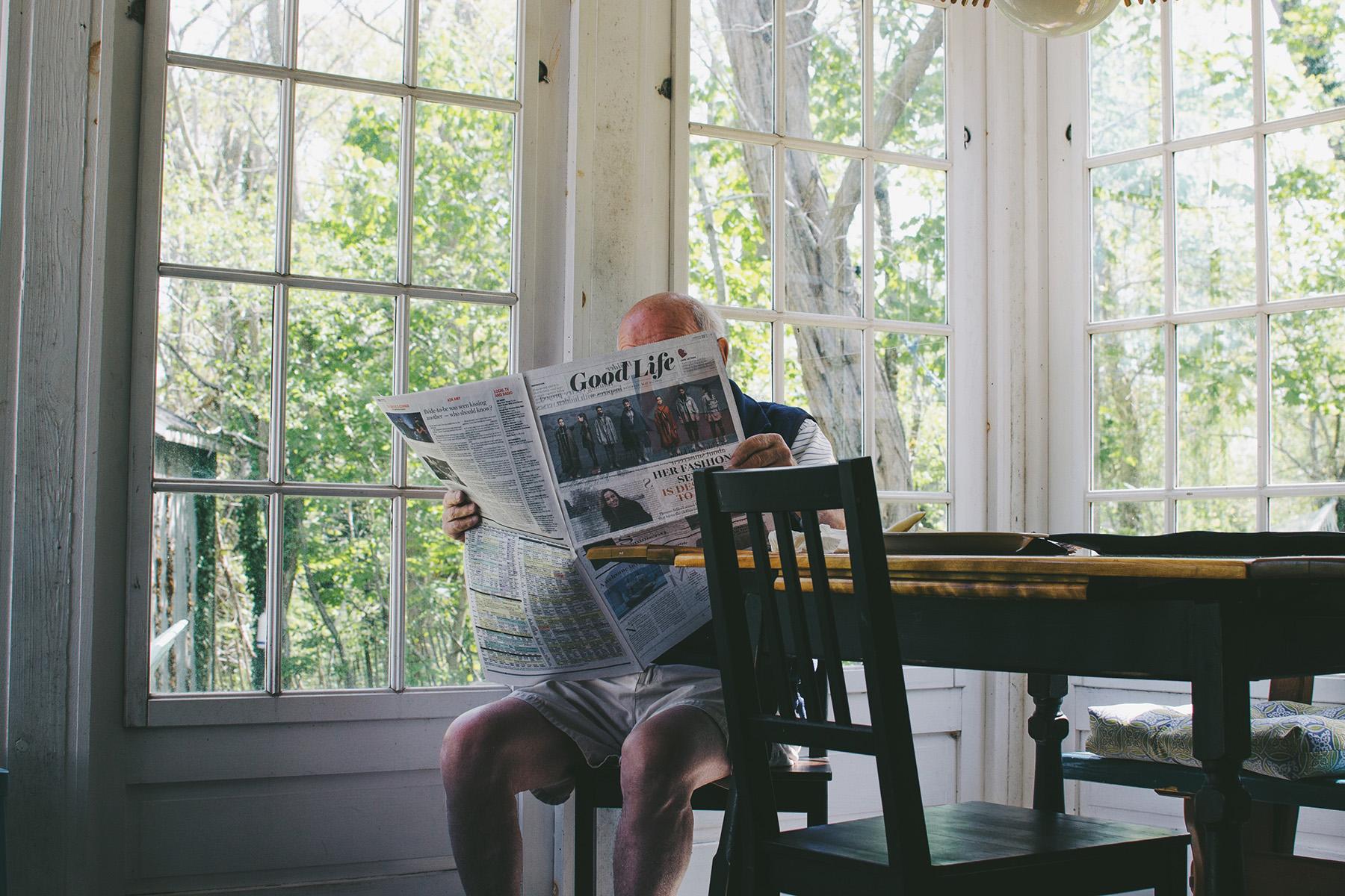 Elderly man reading a newspaper