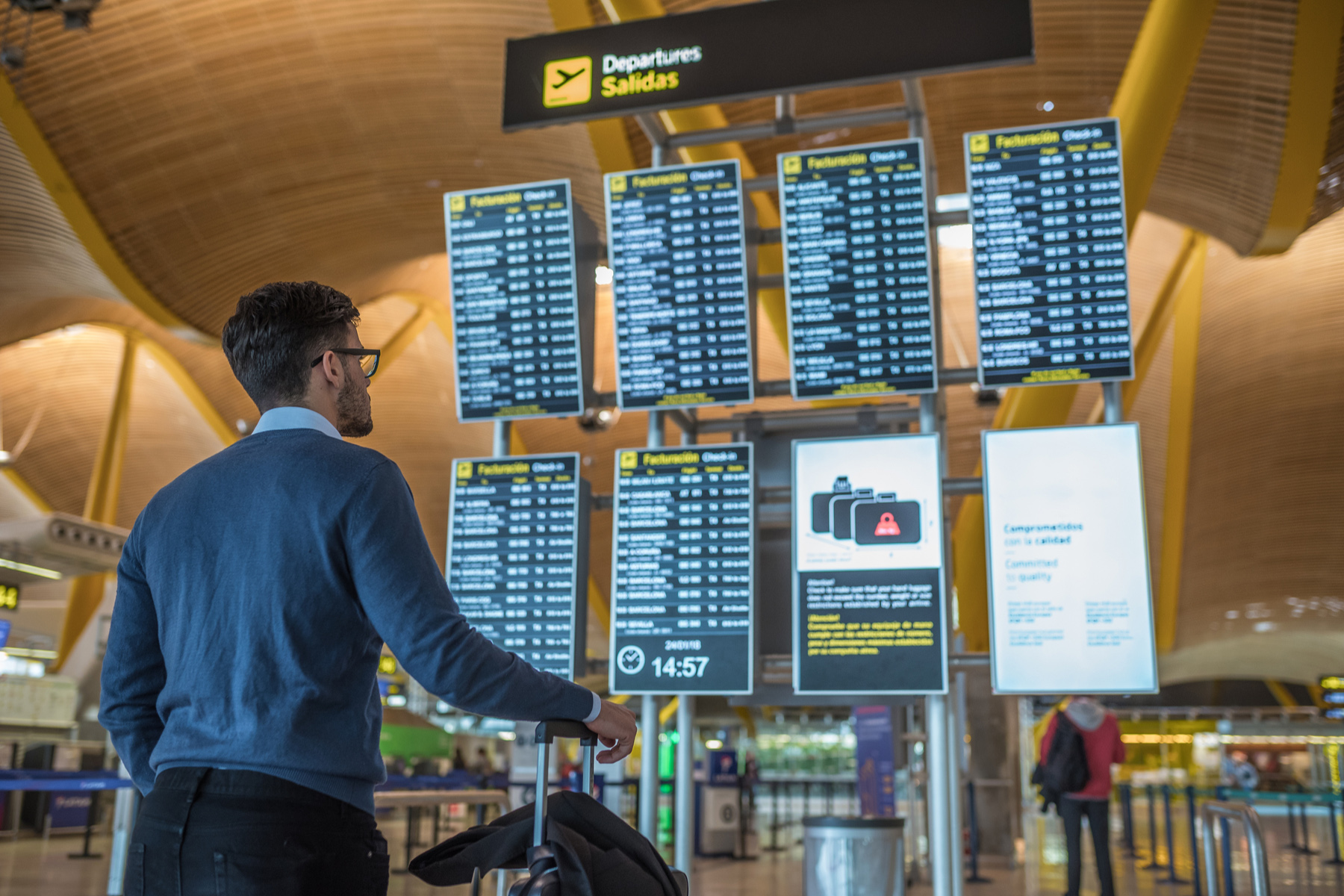 Man reading a departure board at an airport