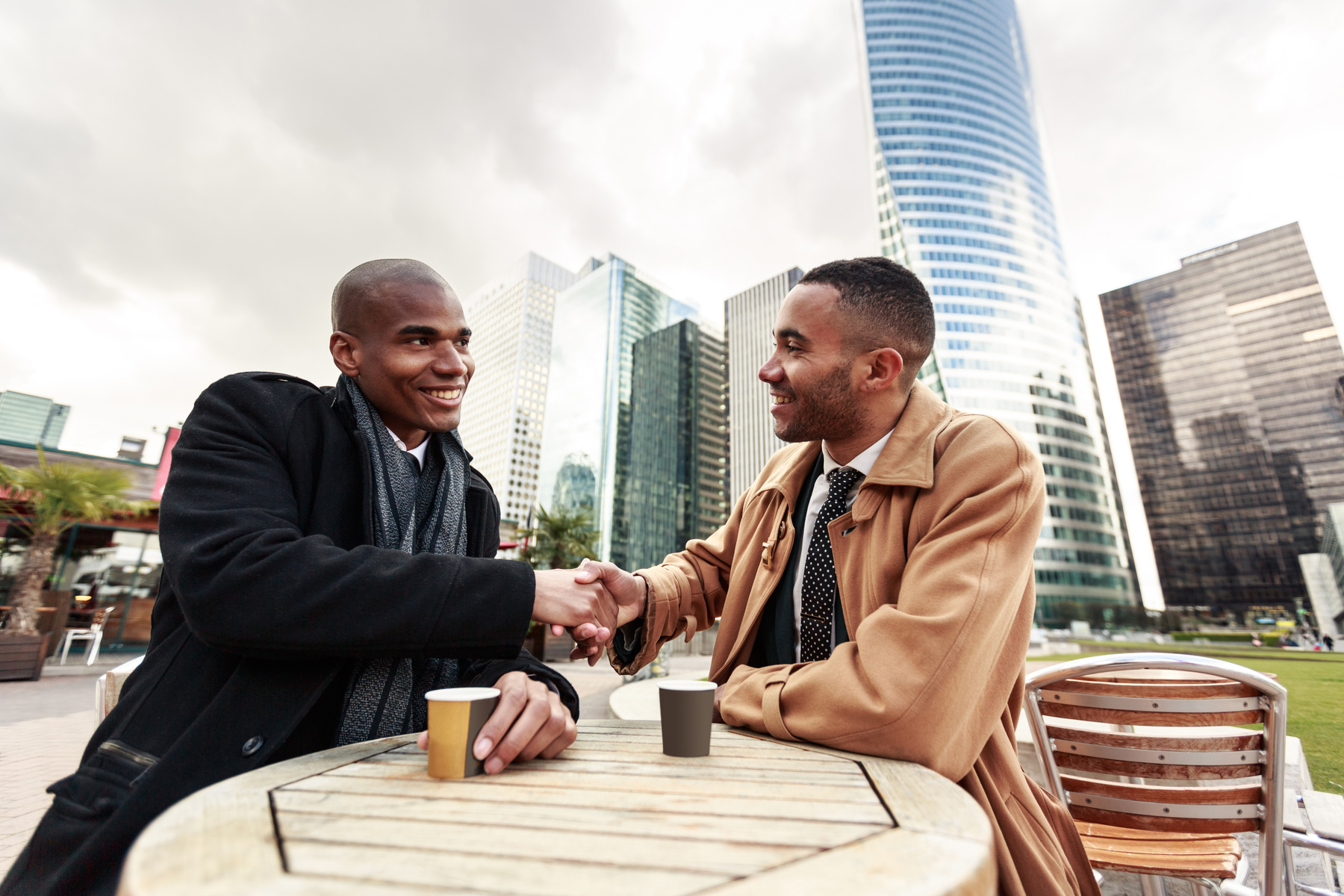 Two colleagues meeting over a coffee outside