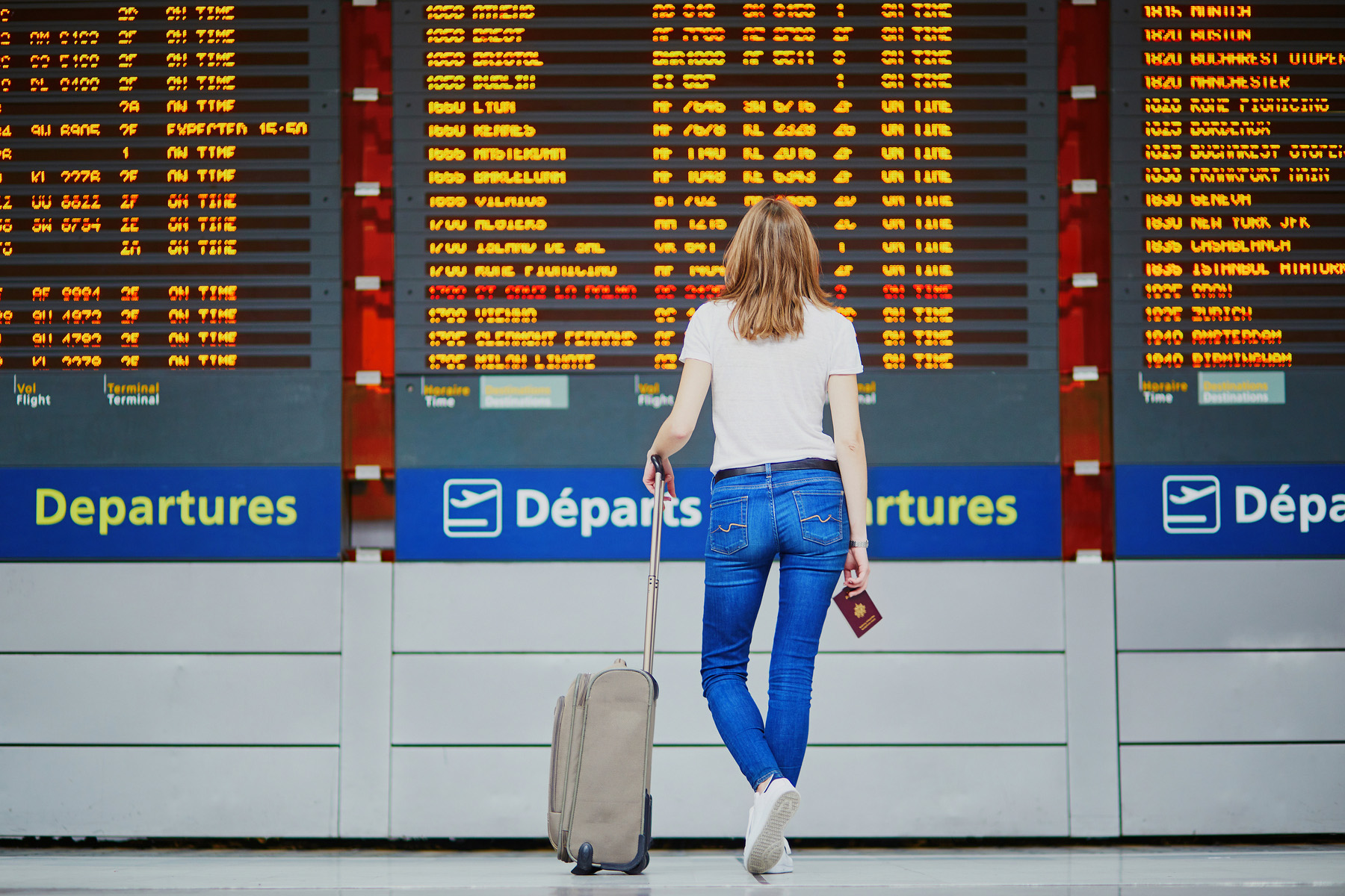 Young woman looking at an airport departure board