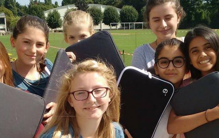 International school girls holding laptops