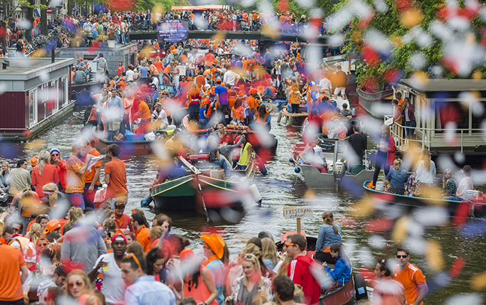 people celebrating king's day on the channels of amsterdam