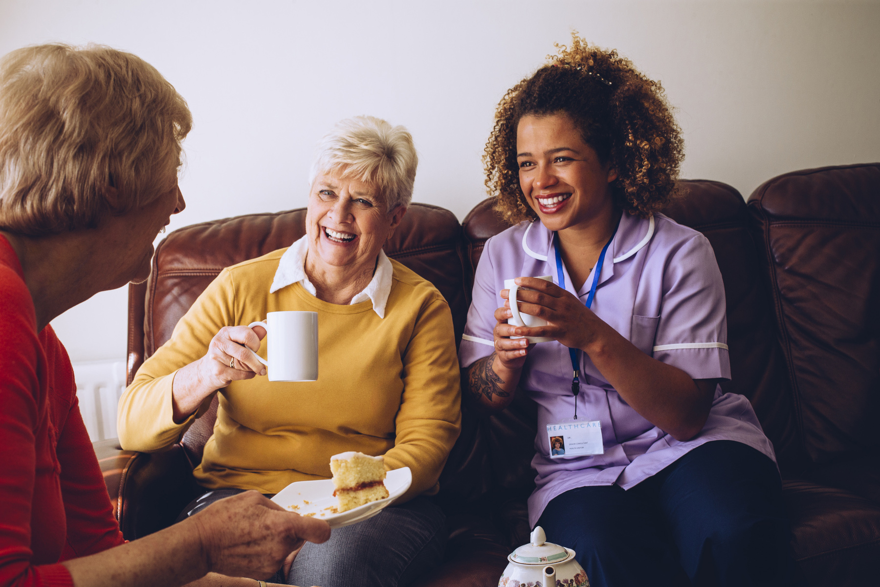Care at home: care worker sitting with two of her live-in care patients