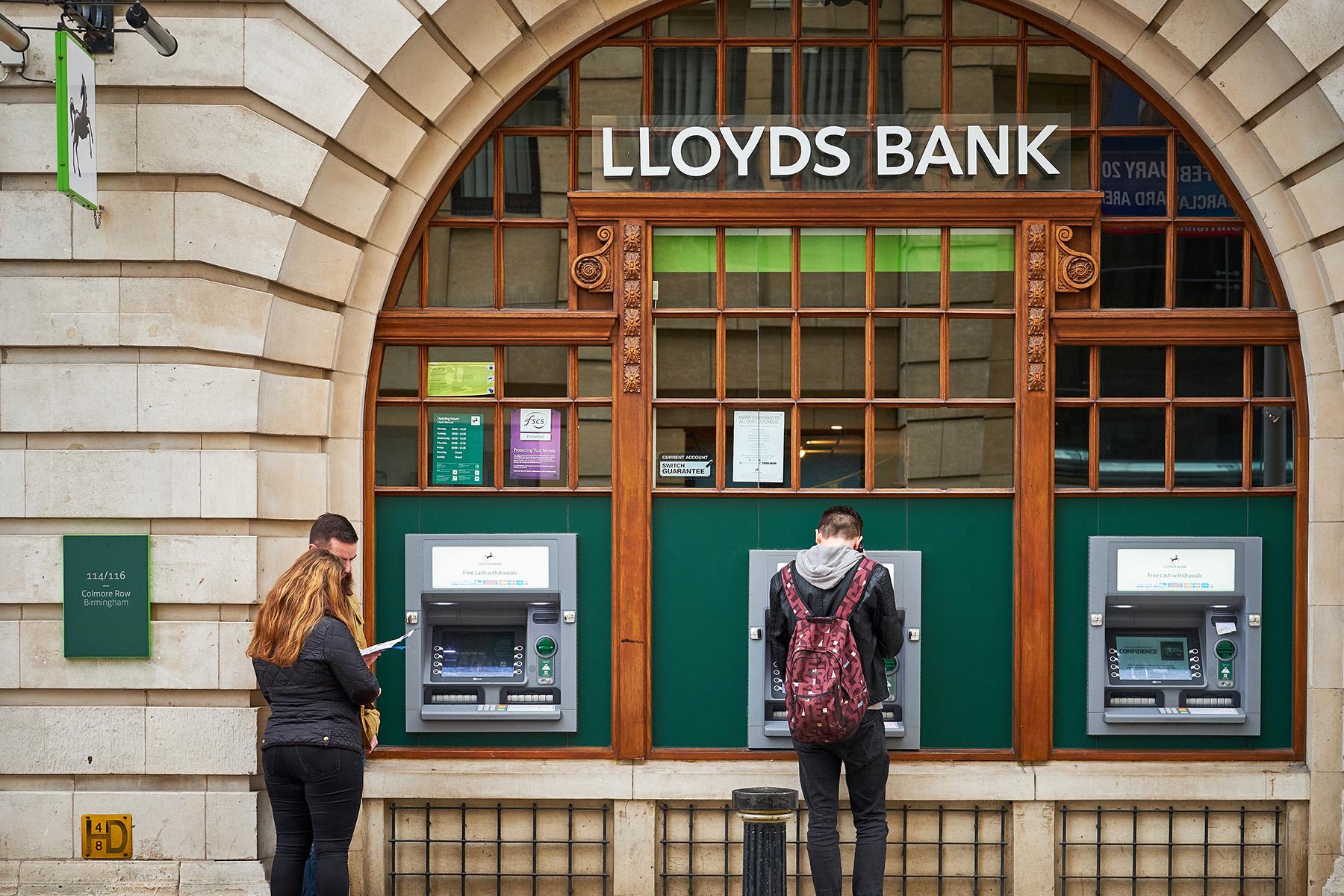 Customers using ATMs at a Lloyds Bank