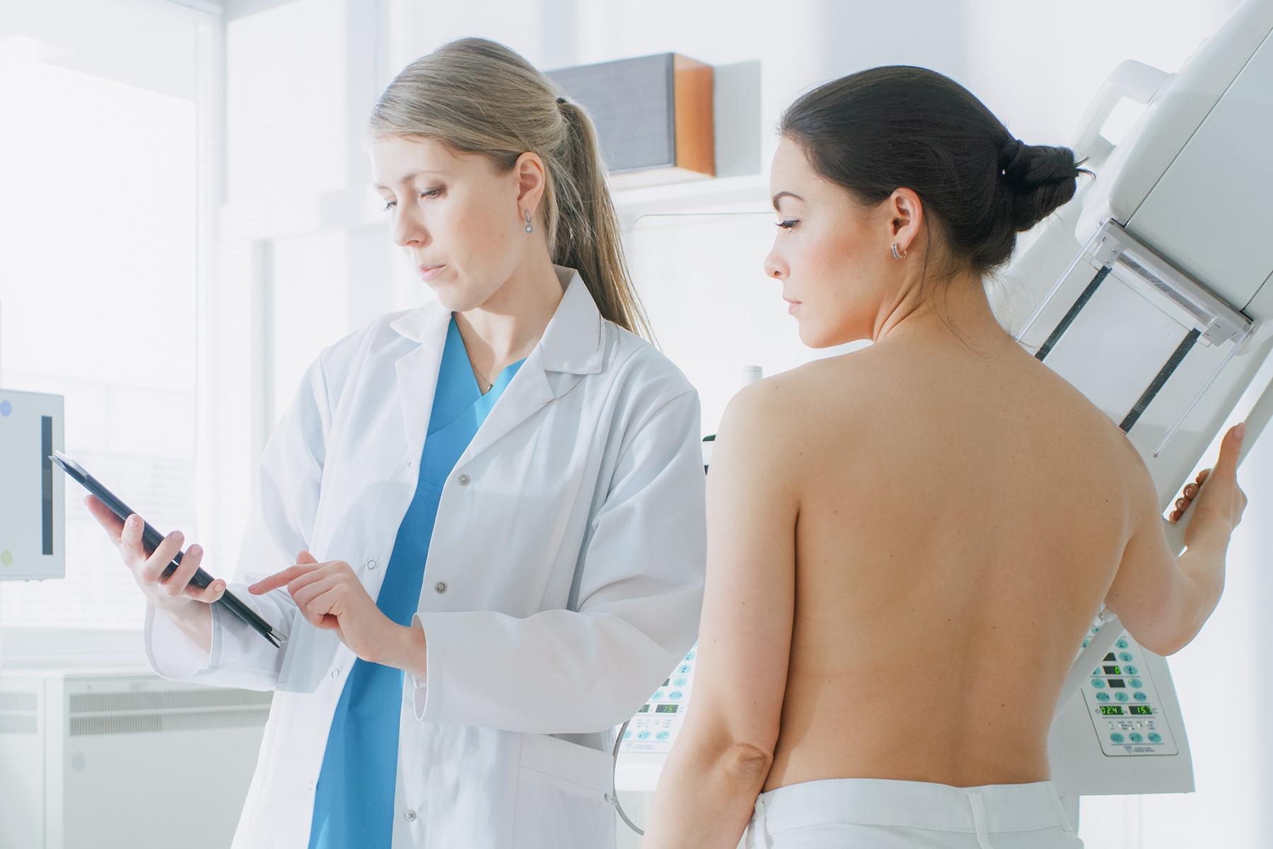Doctor adjusting mammogram machine for a patient
