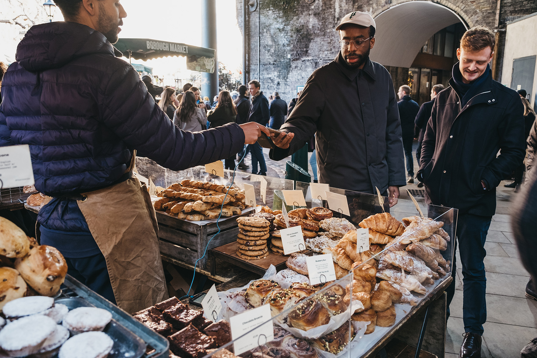 A man makes a payment with his mobile phone at a market in London