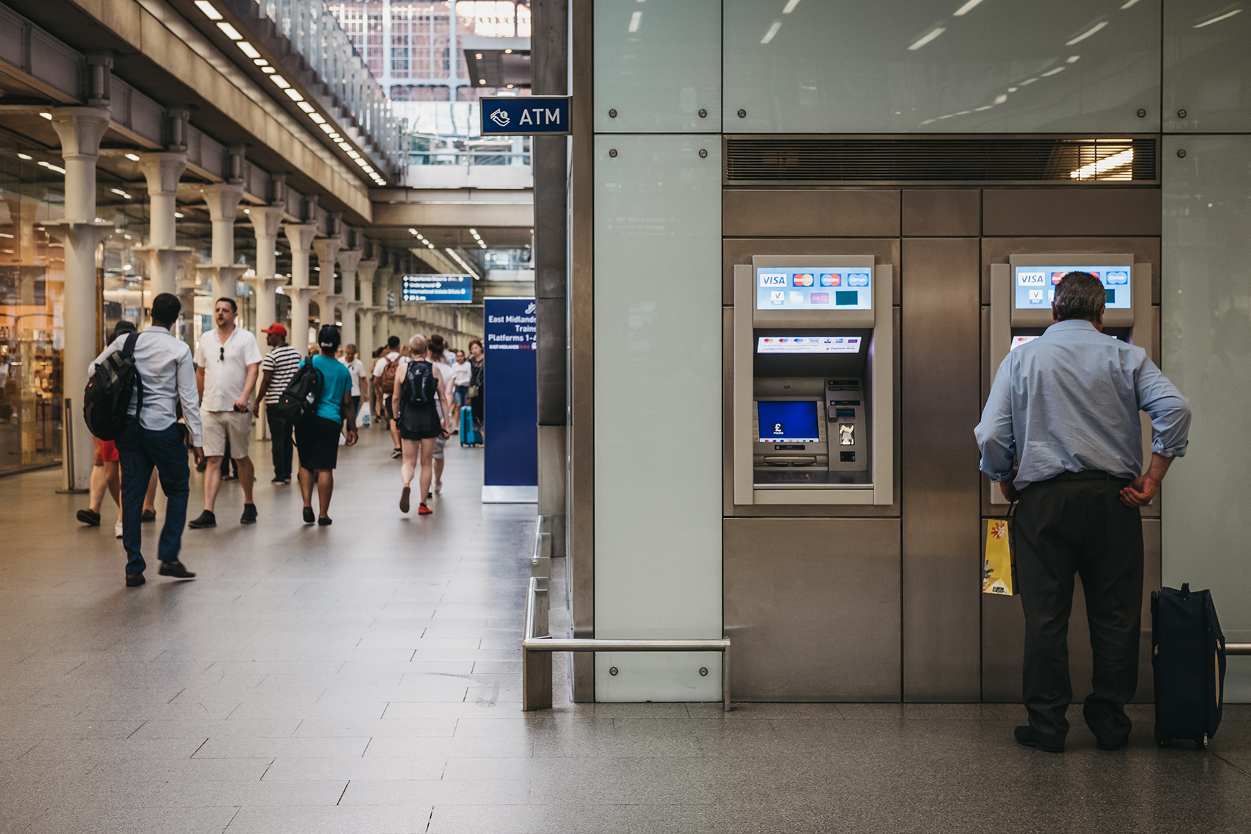 A man uses an ATM at St Pancras station
