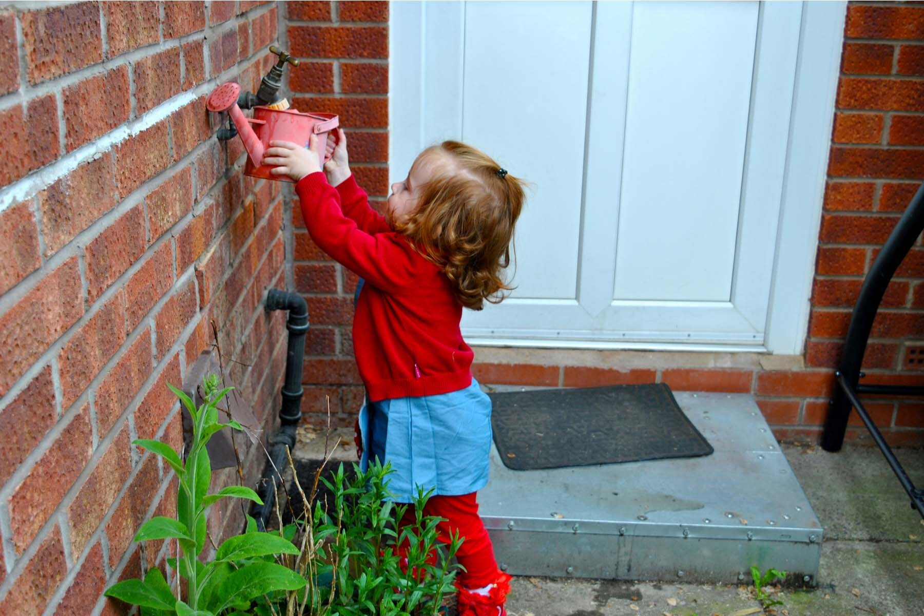 sustainable living in the UK - little girl filling watering can