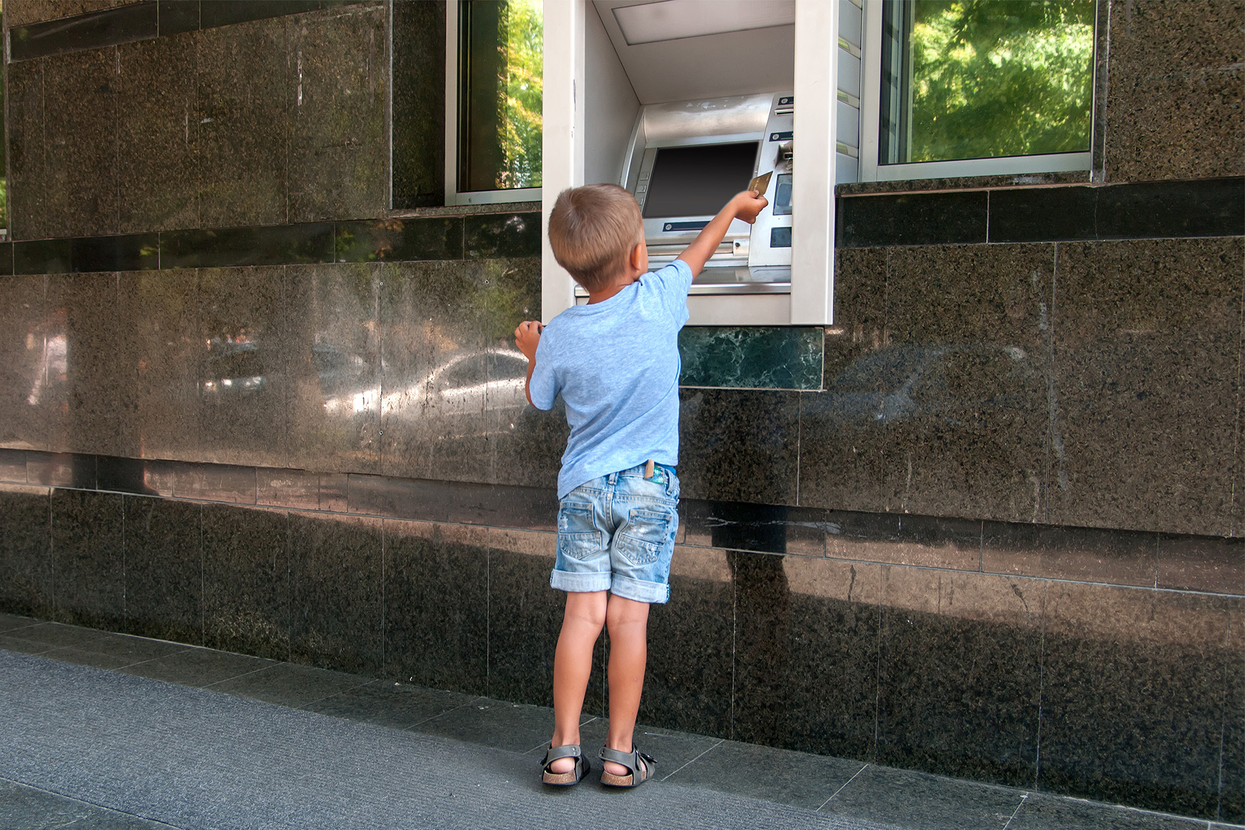 Young boy using ATM