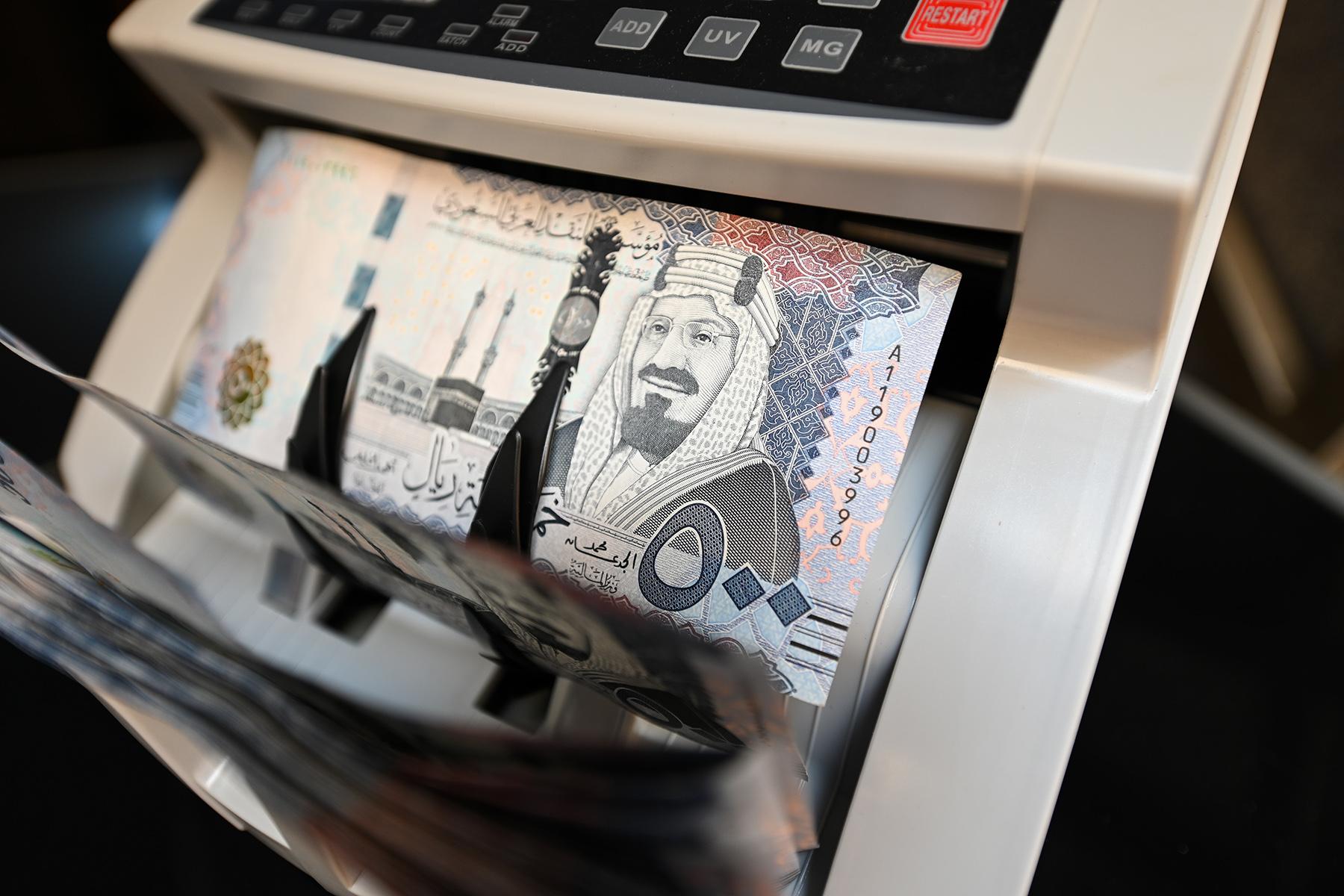 Saudi riyal banknotes in a counting machine