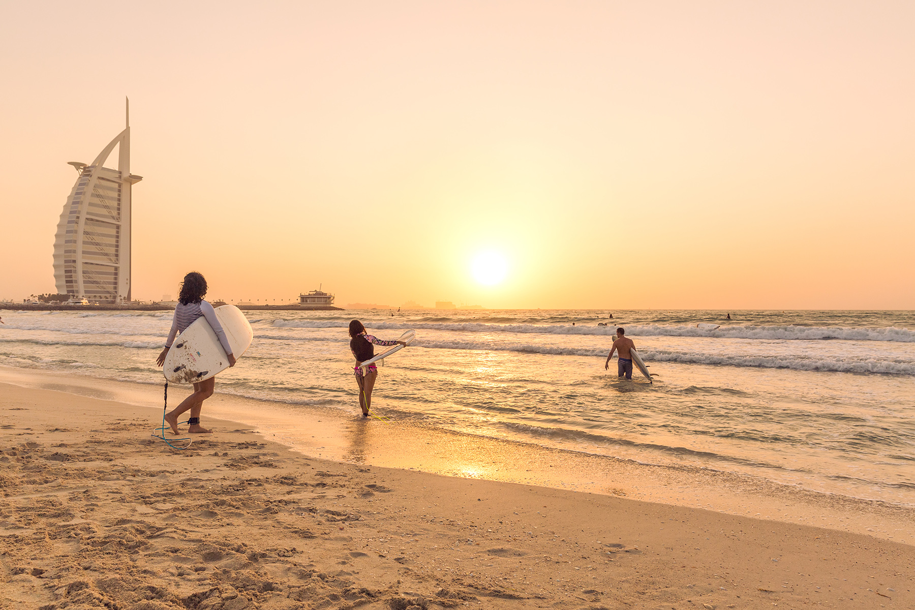 Surfers at sunset in Dubai