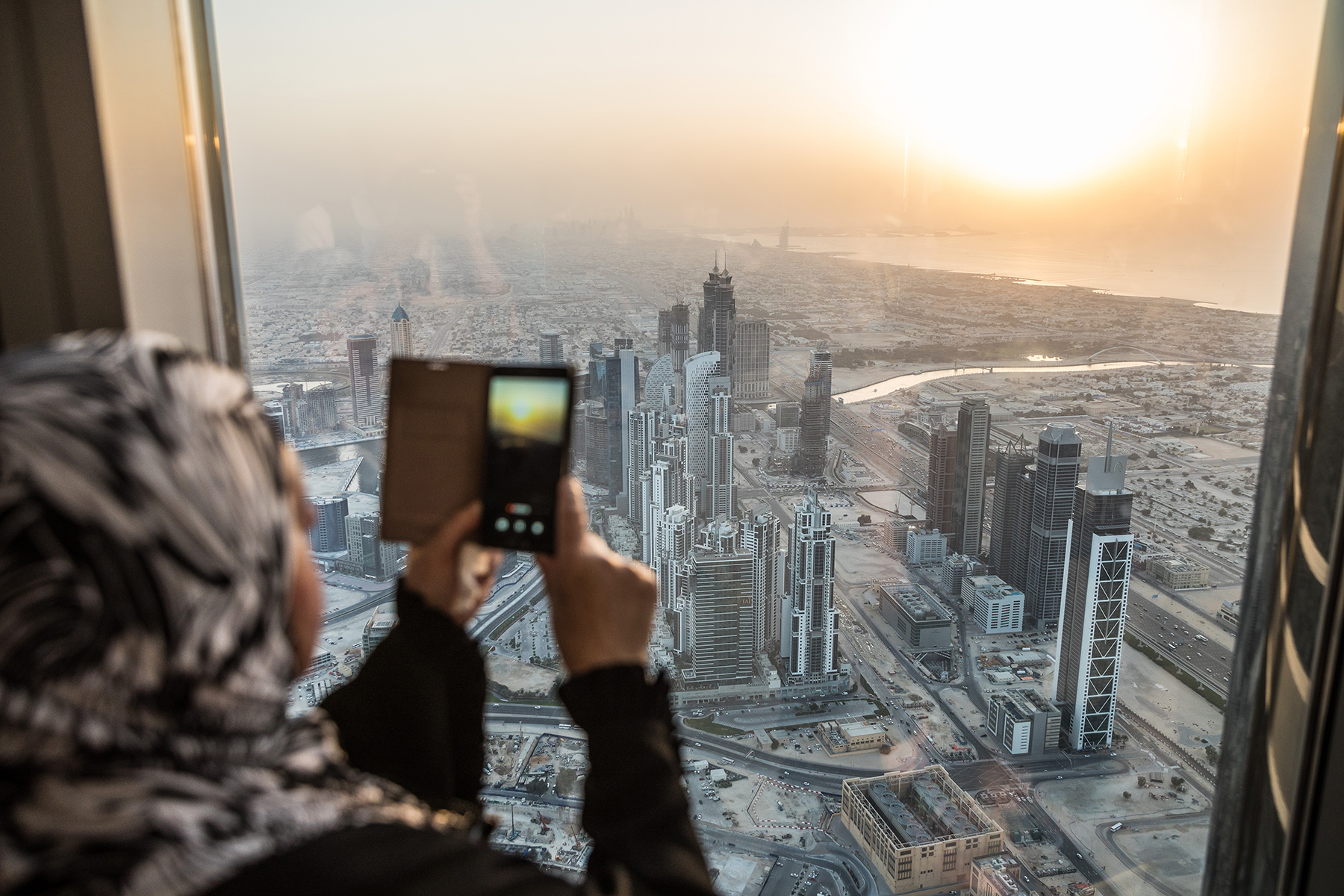 Woman taking a photo of Dubai with her mobile phone