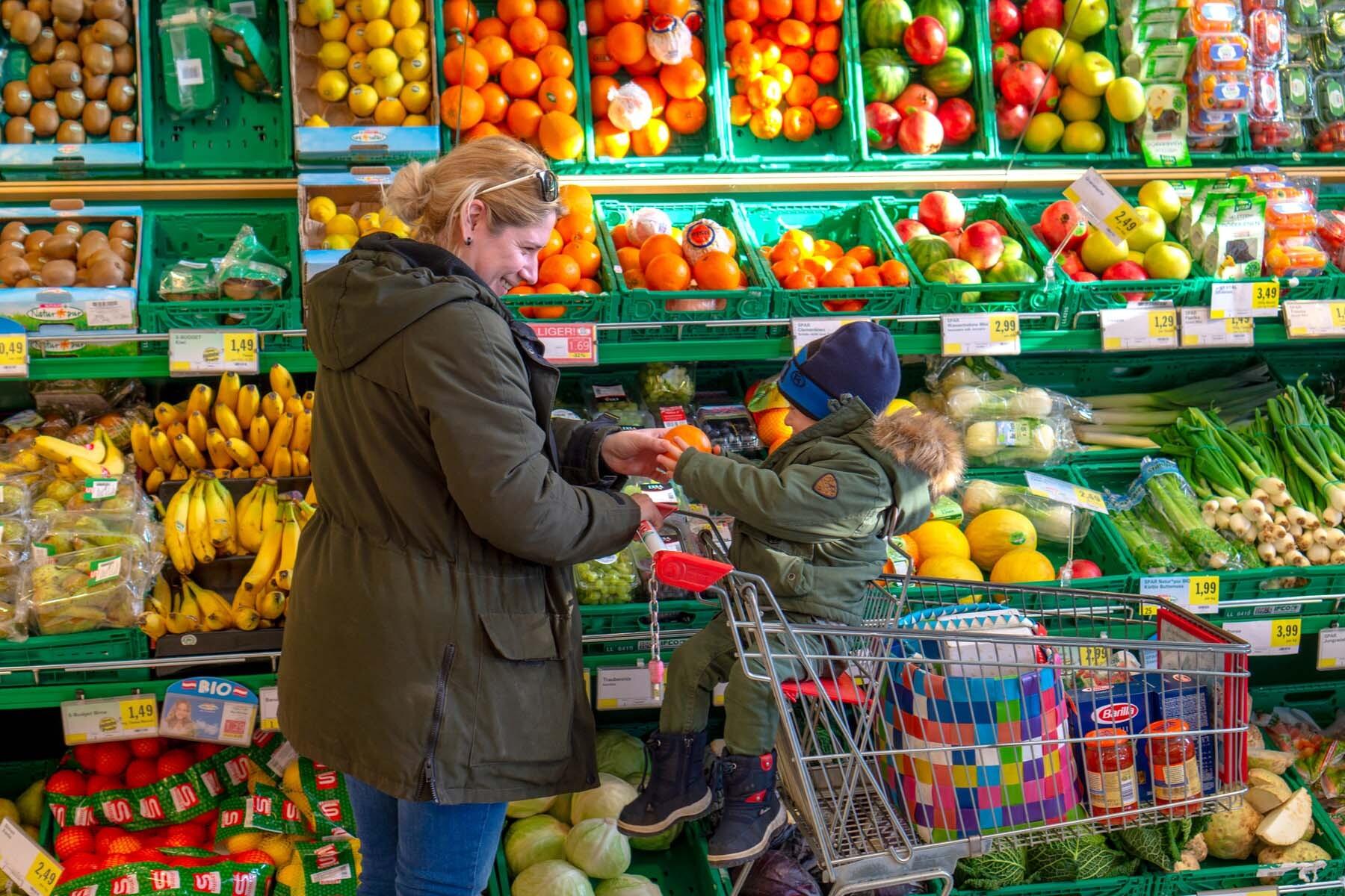 woman pushing child in shopping cart