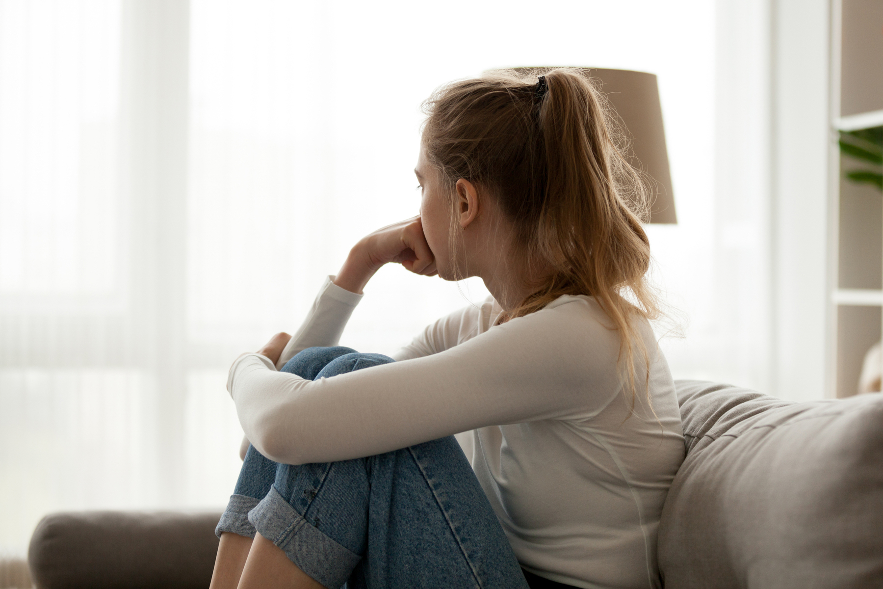Pensive woman sitting on a couch