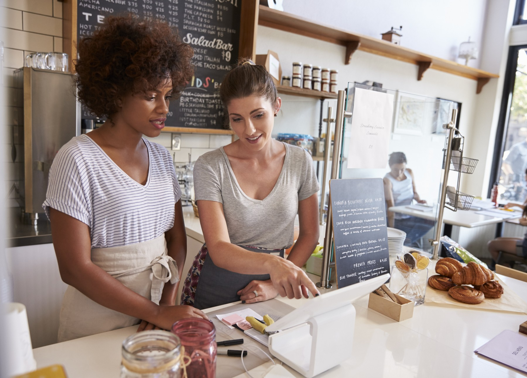 Spain job training, woman explaining cafe work to another woman