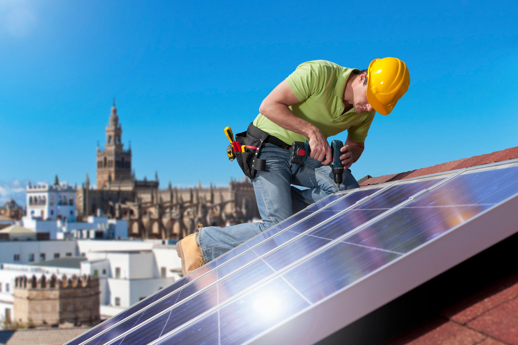 man installs solar panels on roof in Spain