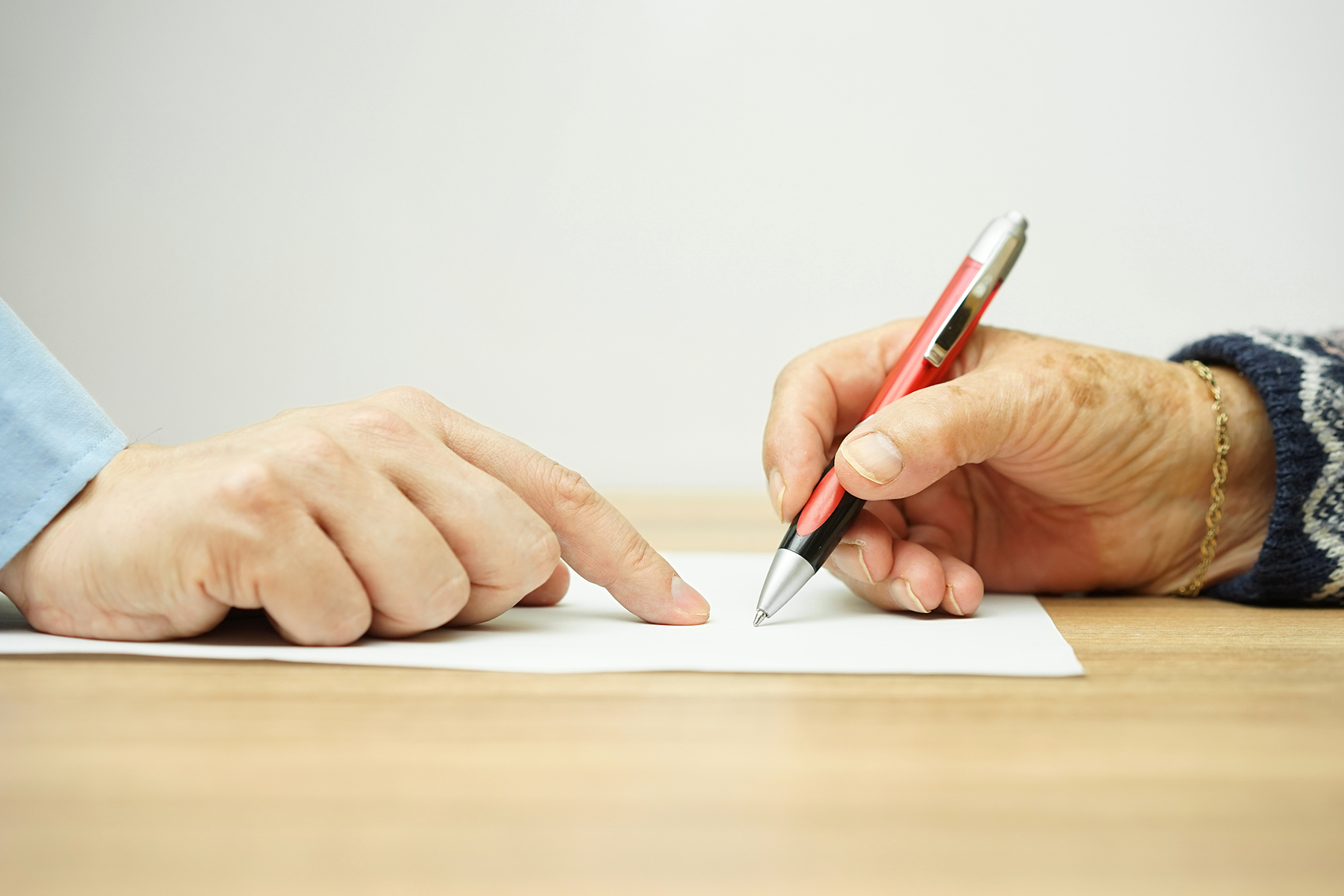 Elderly woman signing contract