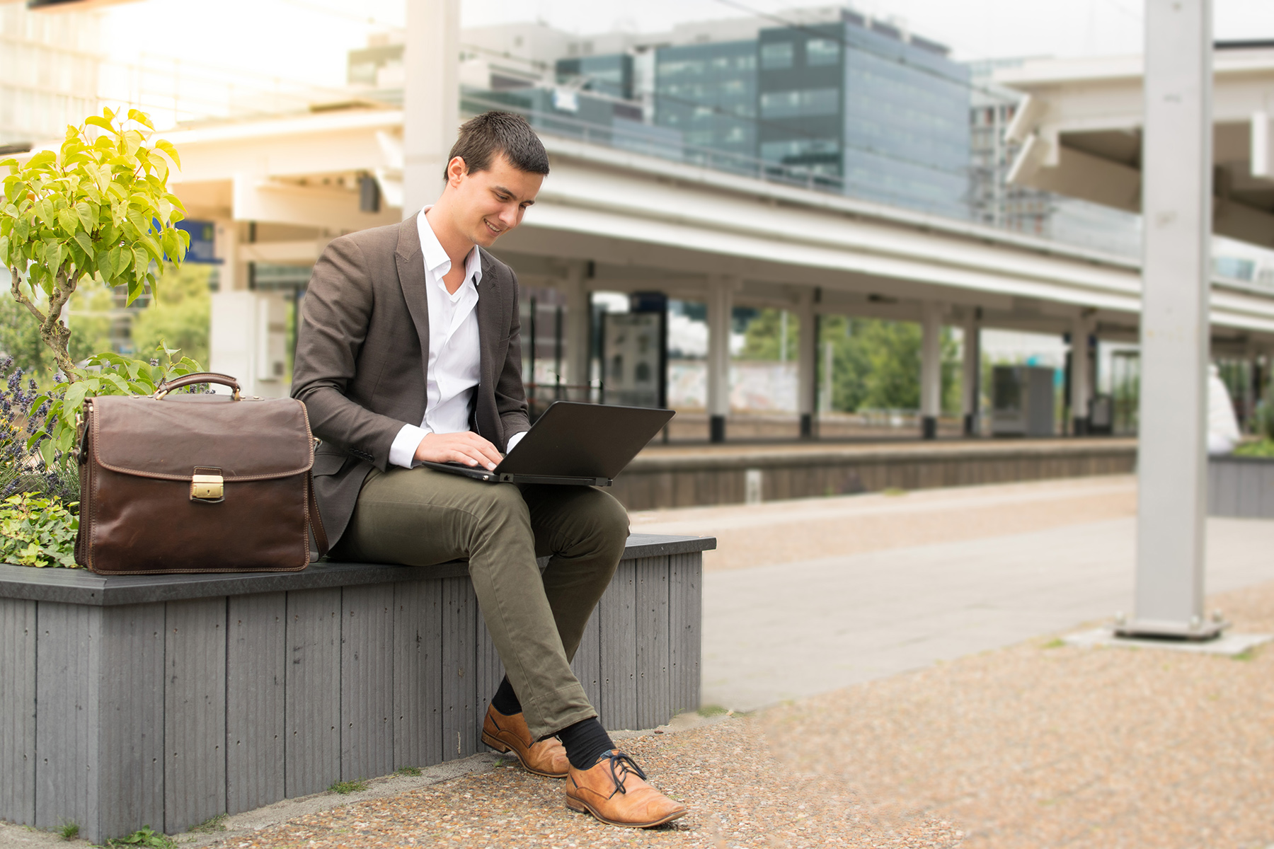 A freelancer works on his laptop at a Dutch train station