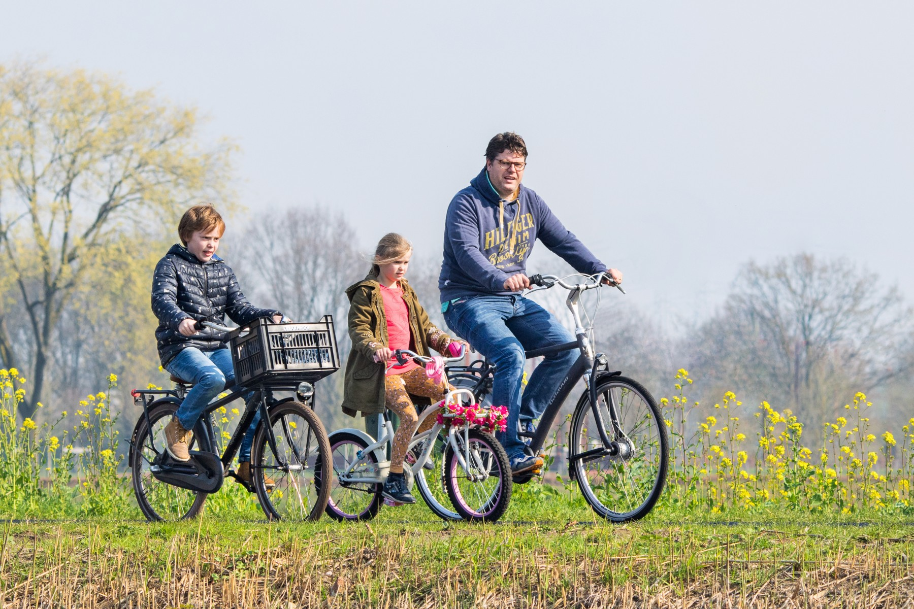 Raising kids in the Netherlands, man and children cycling