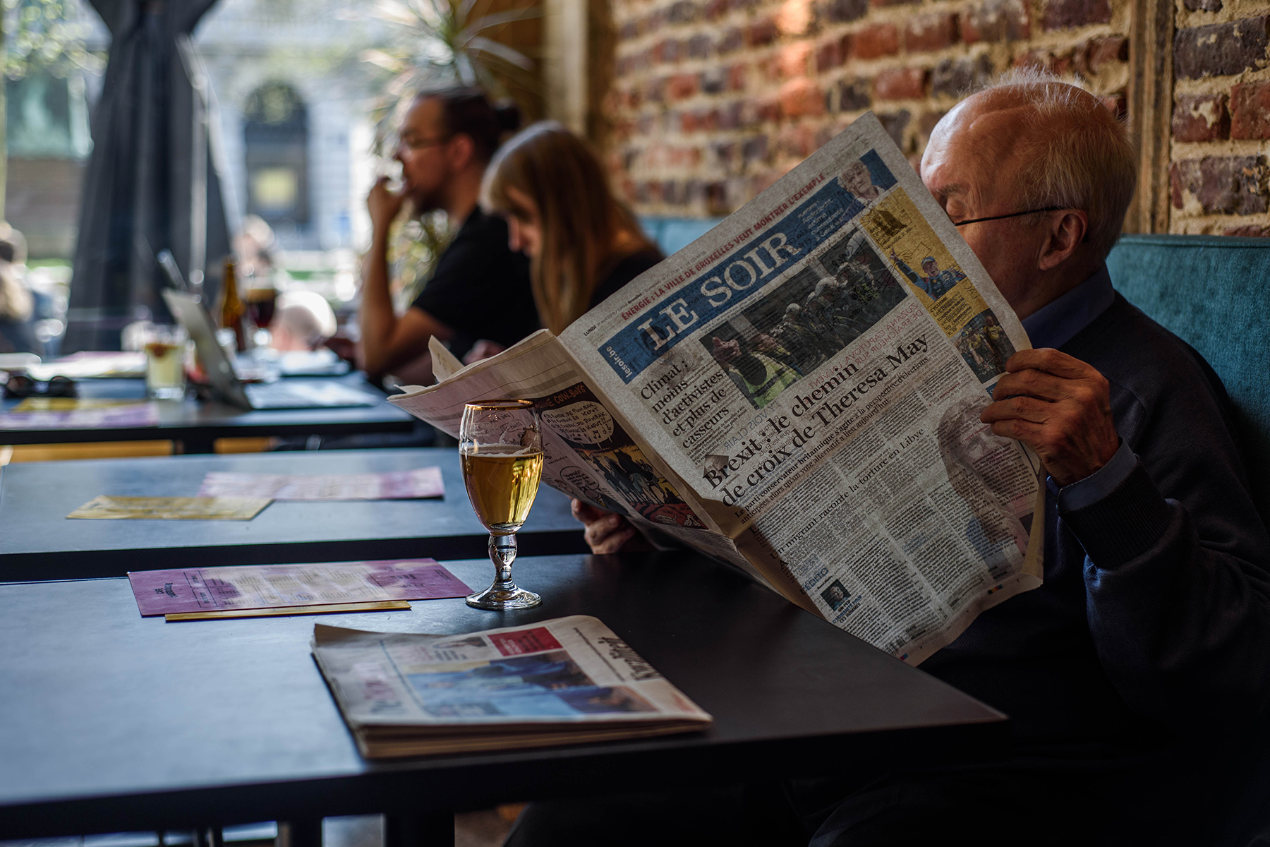 Man in a Brussels café reading the newspaper over a beer