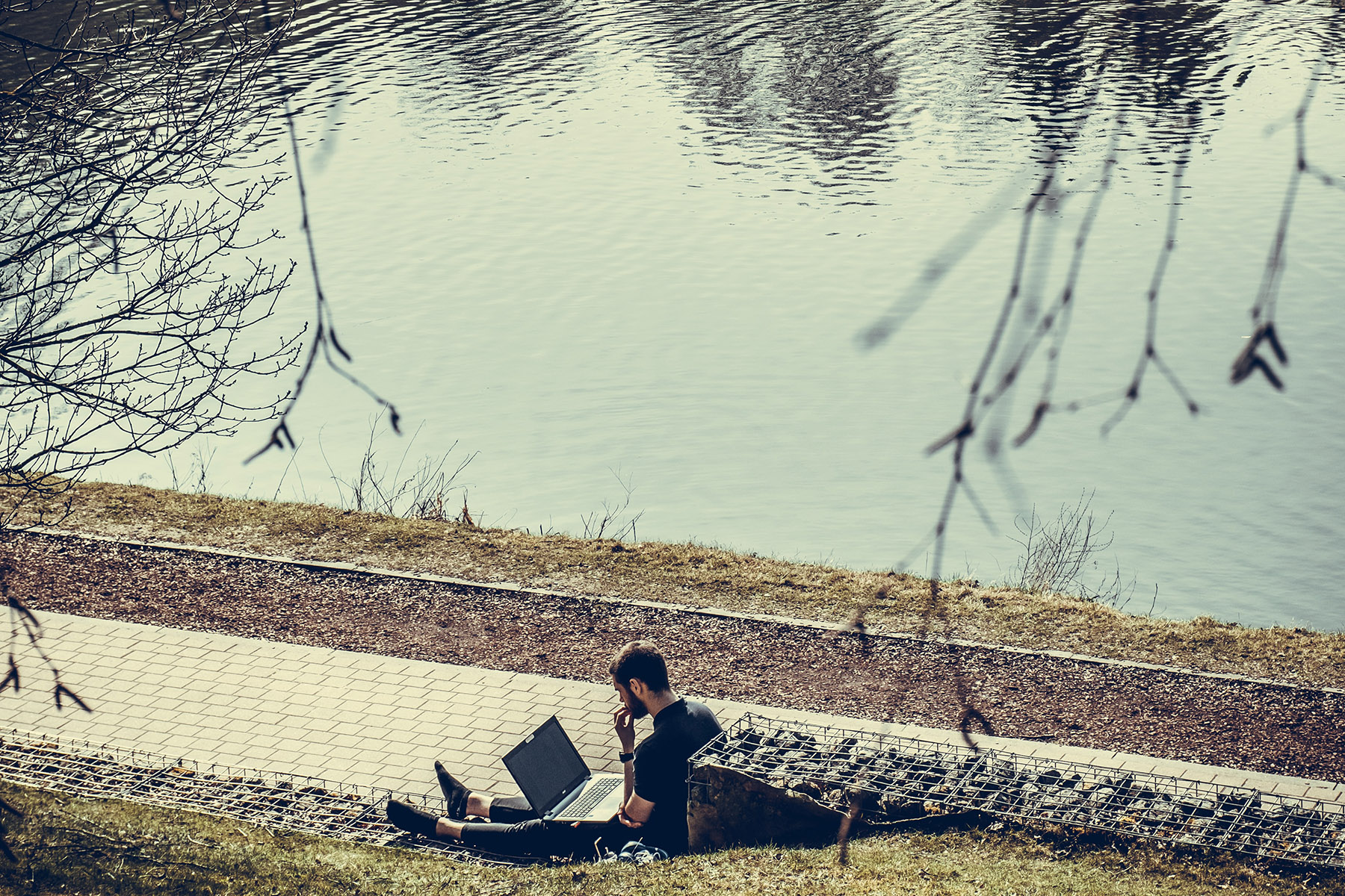 A student working on his laptop in a park in Louvain-la-Neuve