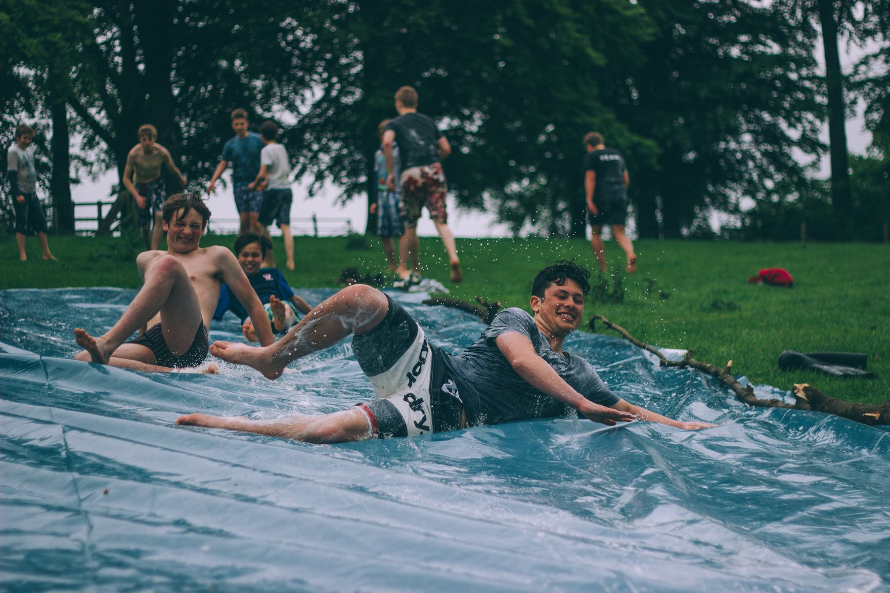 Teenagers on a slip and slide