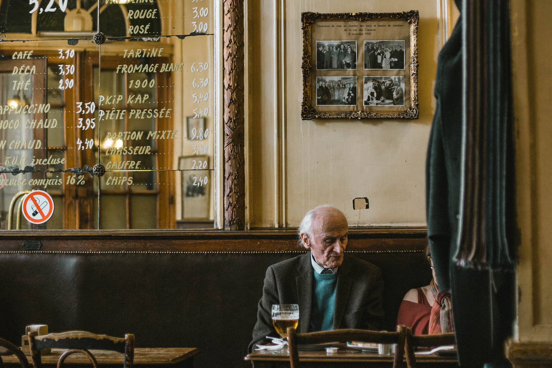 A couple reads the menu in a typical Brussels café