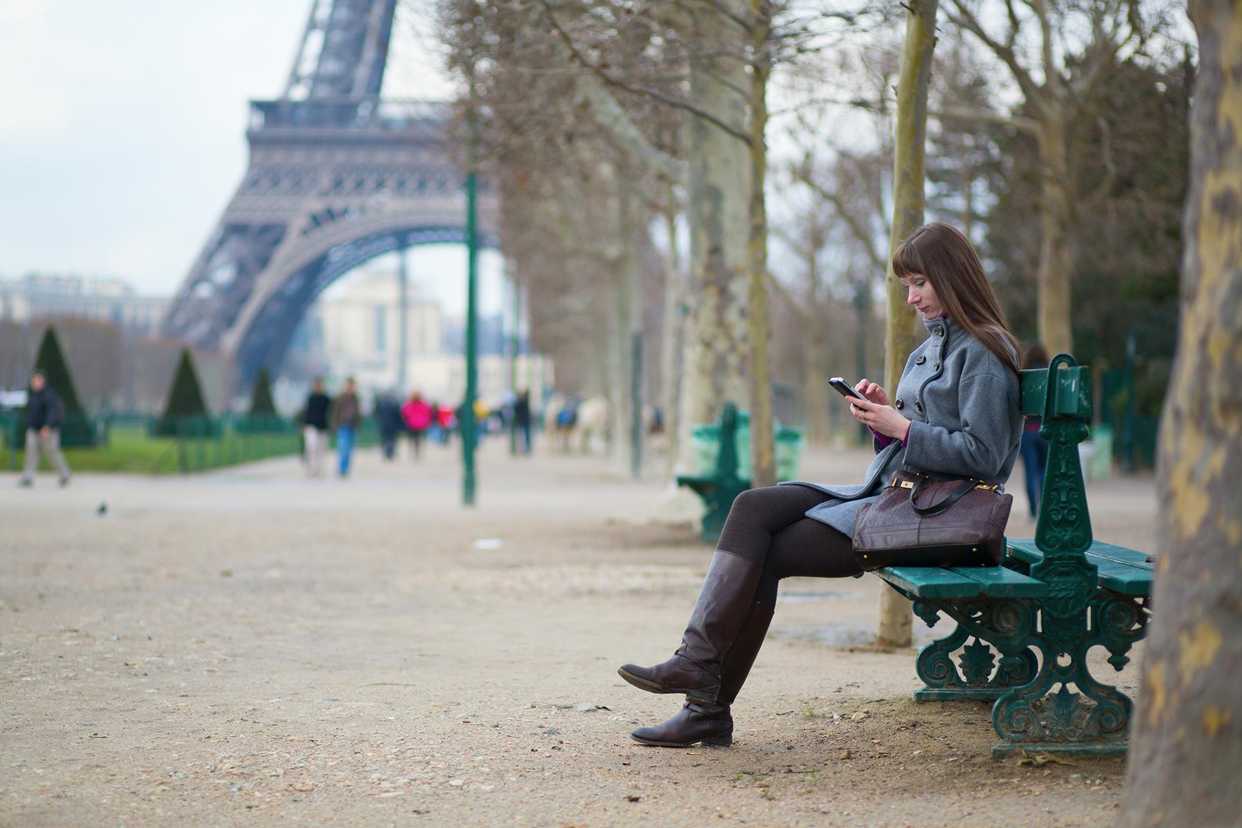 Woman using her mobile phone in Paris