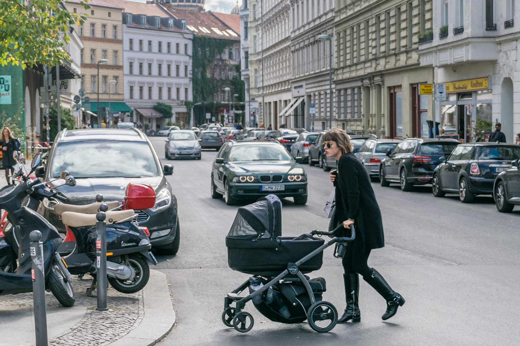 A mother crosses a street with a stroller in Berlin