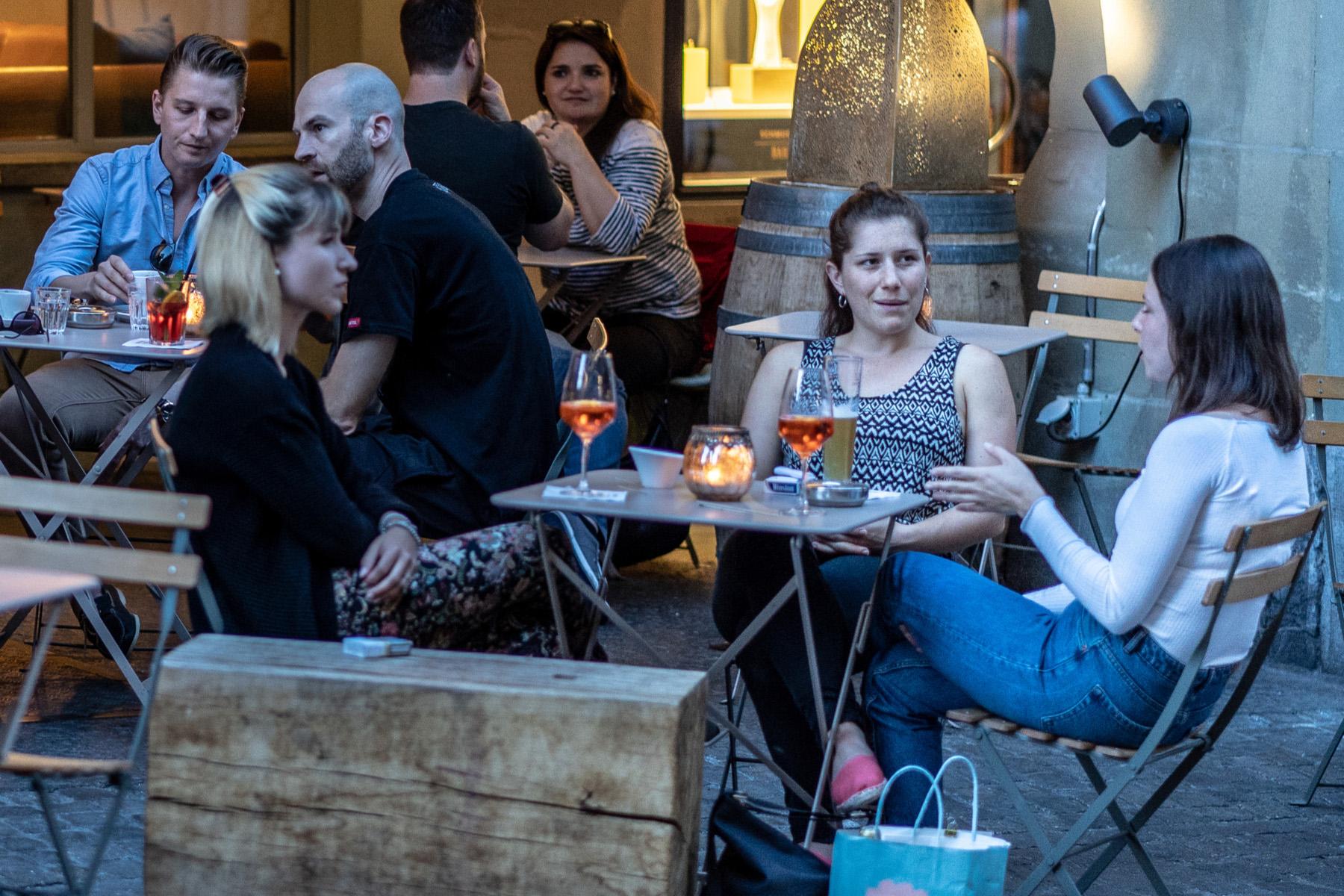 Friends talking over drinks on a terrace