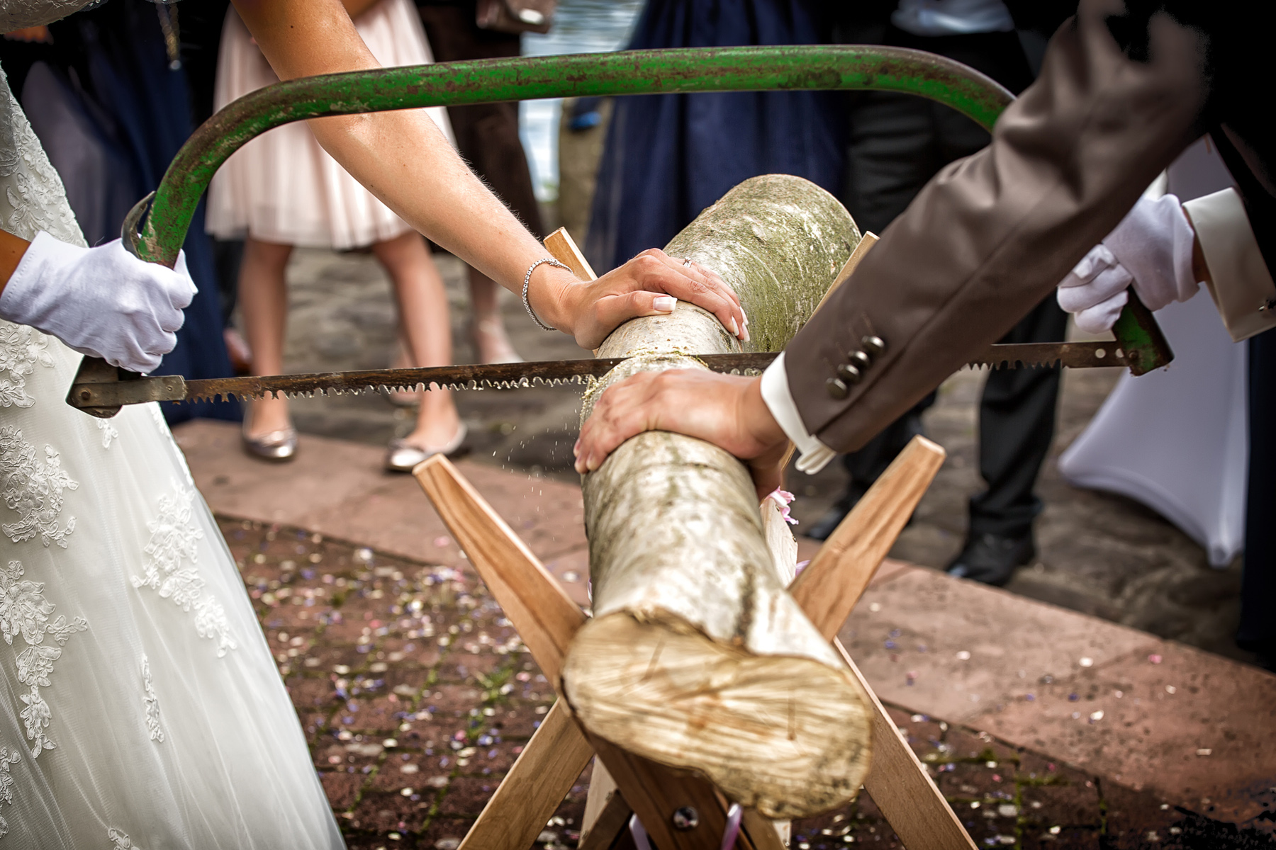 Bride and groom sawing a log at their wedding