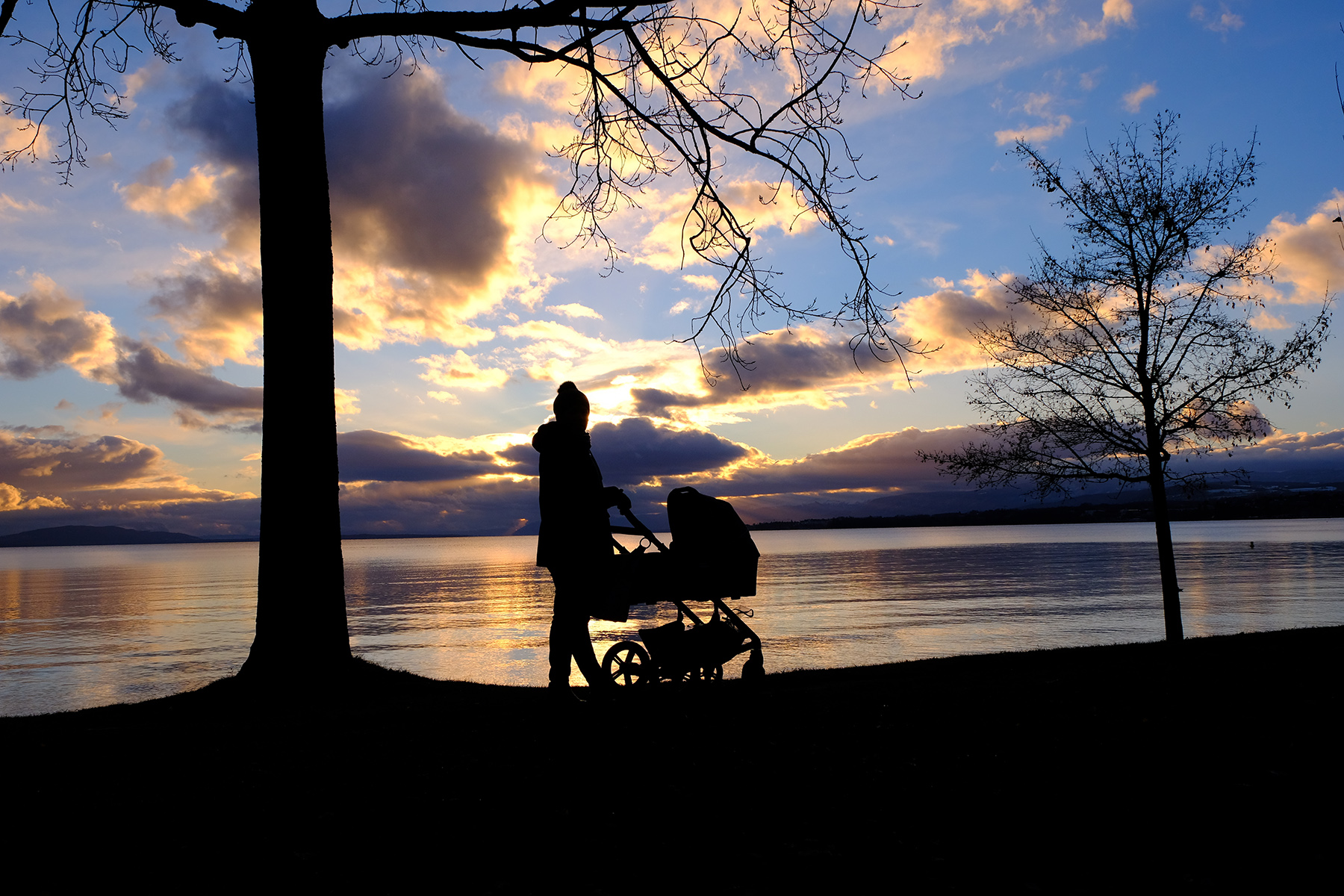 A mother with a baby stroller walking along Lake Geneva