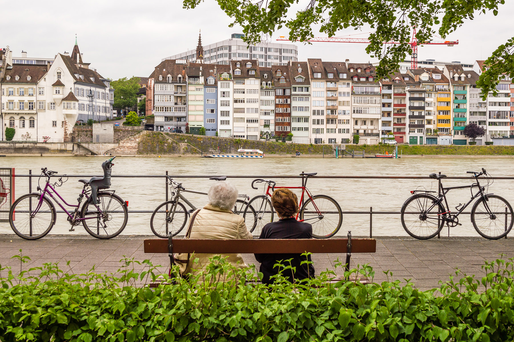Two female retirees admiring a riverside view in Basel