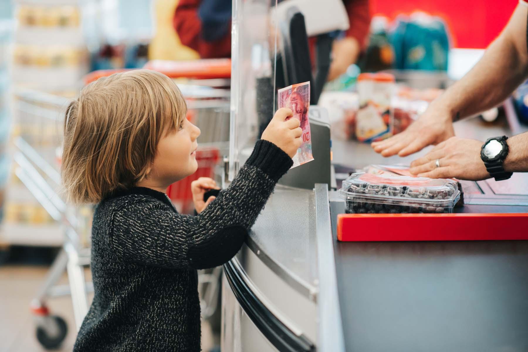 Boy paying Swiss supermarket