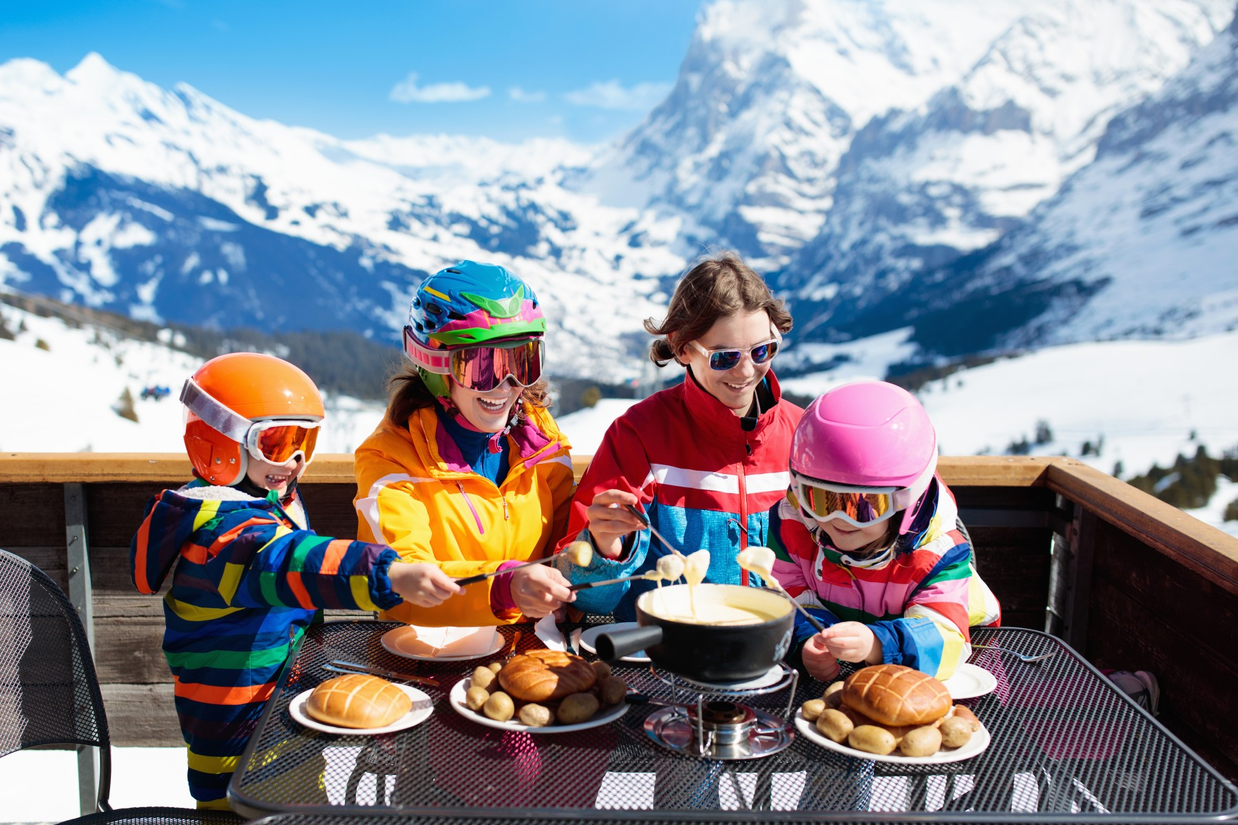 family with young children shares fondue on a ski holiday in Switzerland