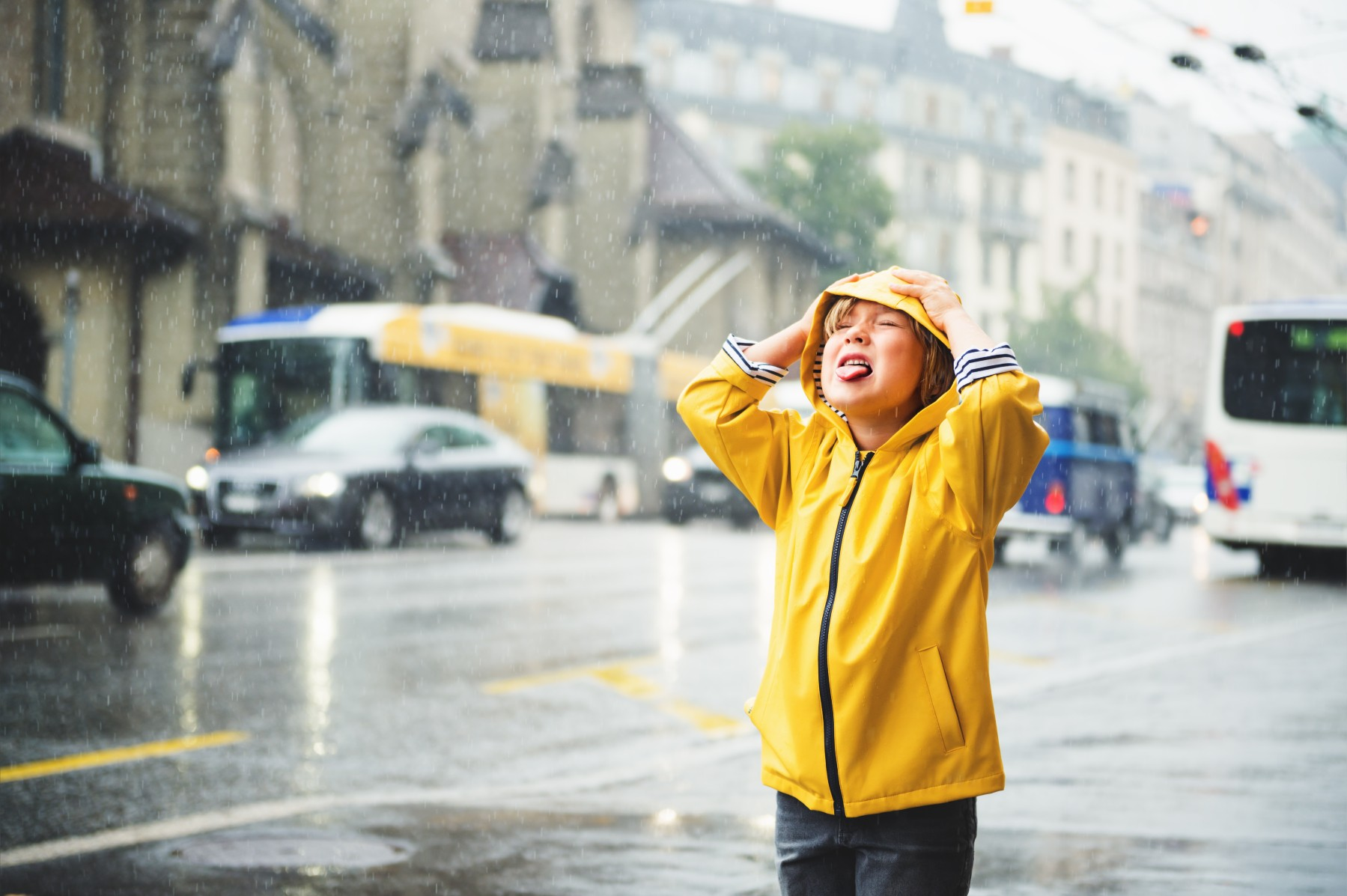 child stands in the rain with tongue out in Switzerland