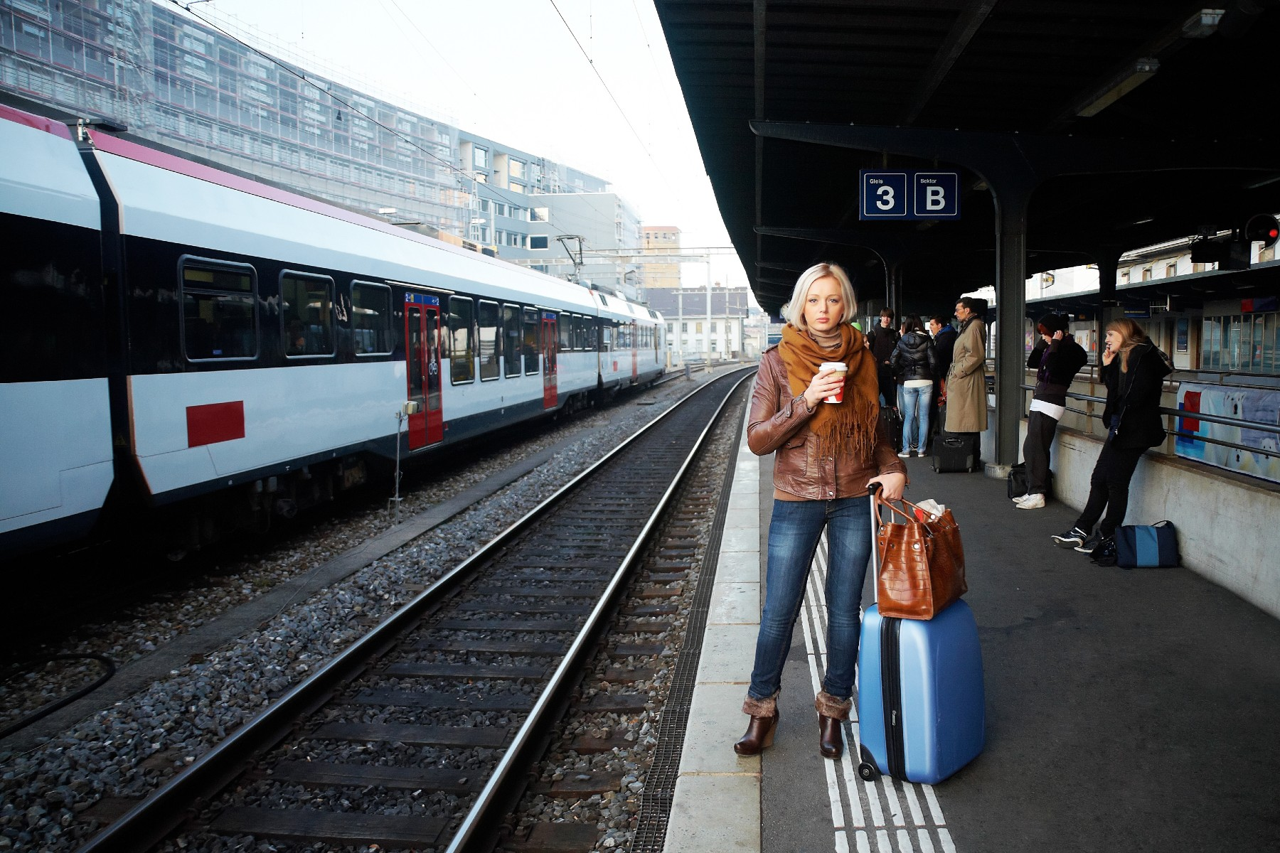 Woman with luggage at train station, train travel Switzerland