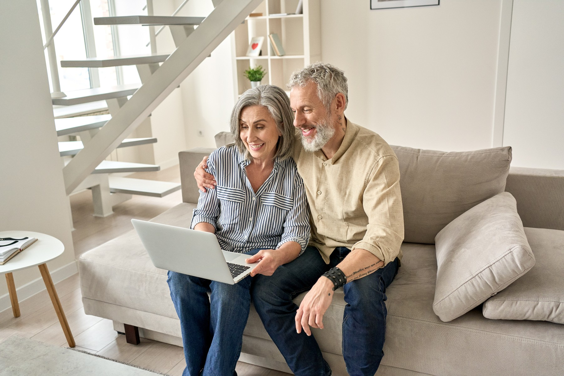 online car shopping in Switzerland, couple on couch with laptop