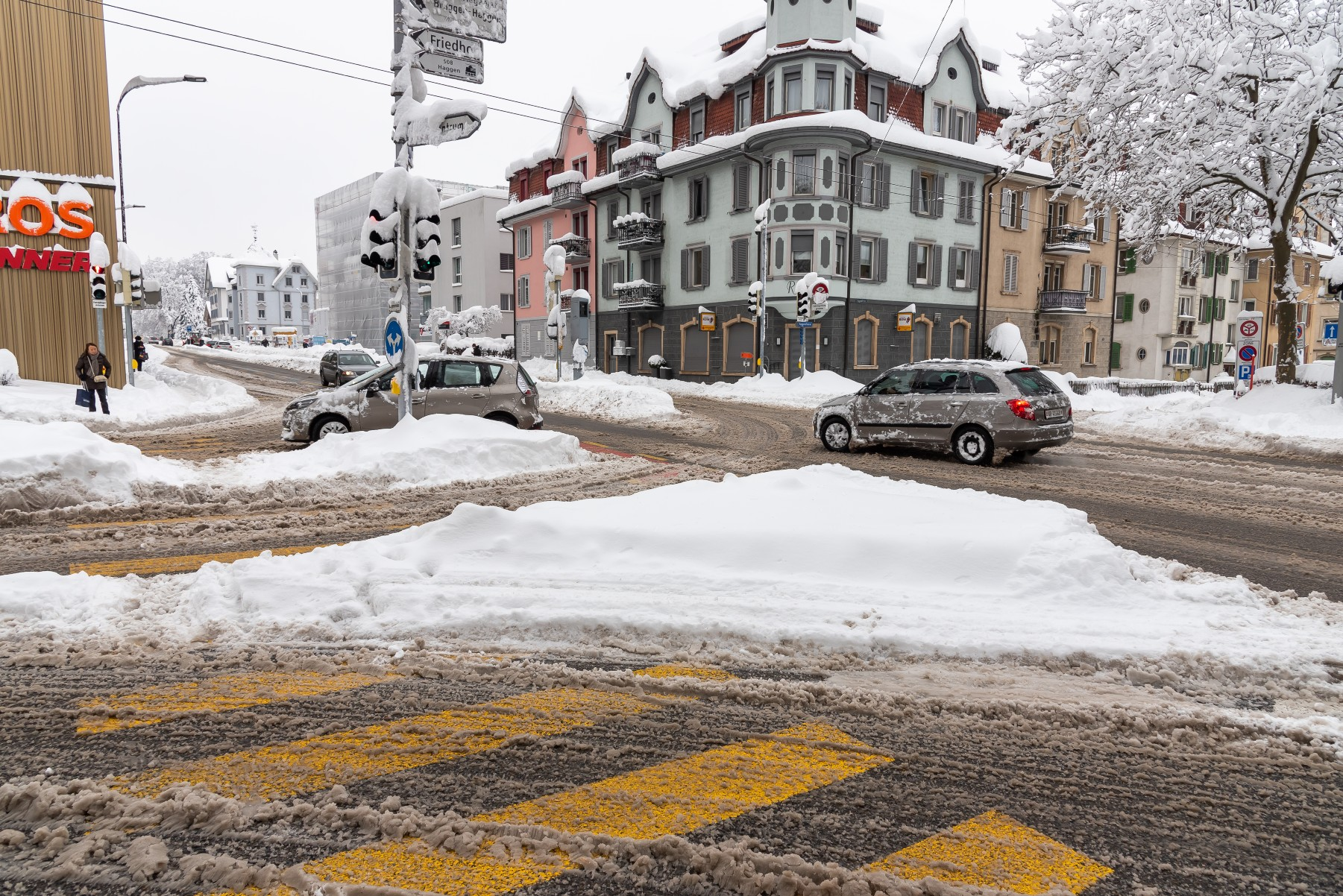cars driving in snow in Swiss city streets