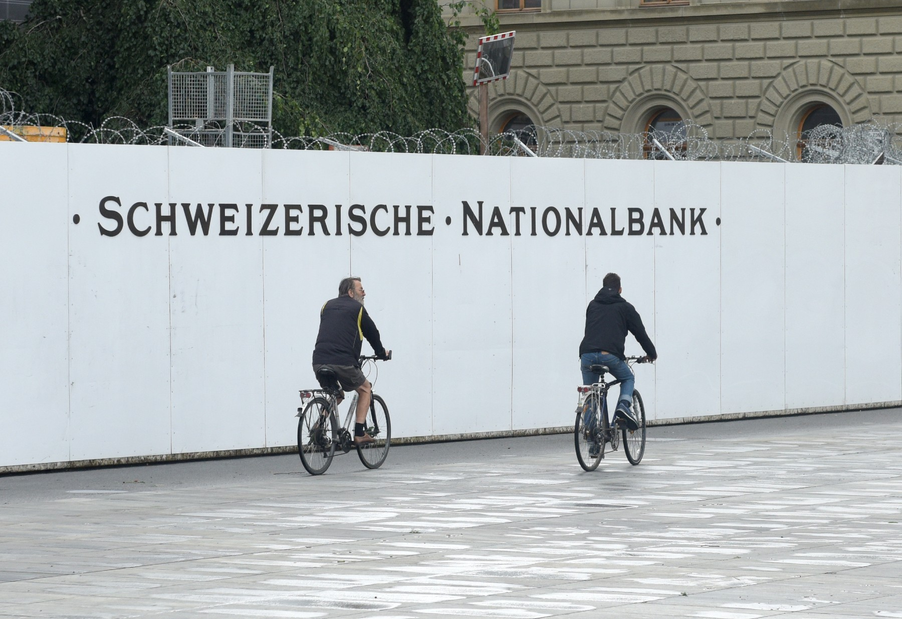 cyclists ride by the Swiss National bank sign, why is Switzerland so rich